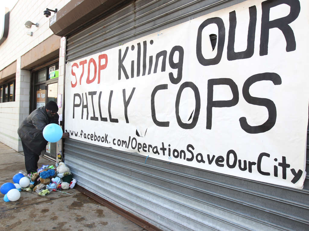 MICHAEL BRYANT / STAFF PHOTOGRAPHER Jerome Mack, of Operation Save Our City, secures a sign over the metal doors of the GameStop where Officer Robert Wilson was killed.