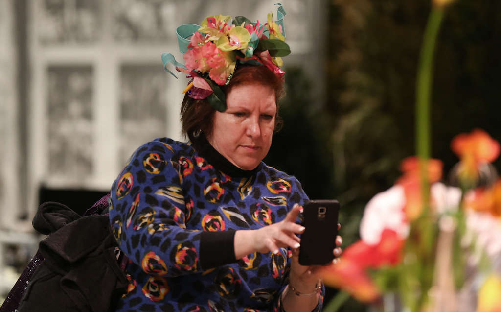 DAVID MAIALETTI / STAFF PHOTOGRAPHER No unwelcomed guests soiled this year´s Flower Show. Elizabeth Plepis shows there´s no harm in taking a floral-crown selfie.