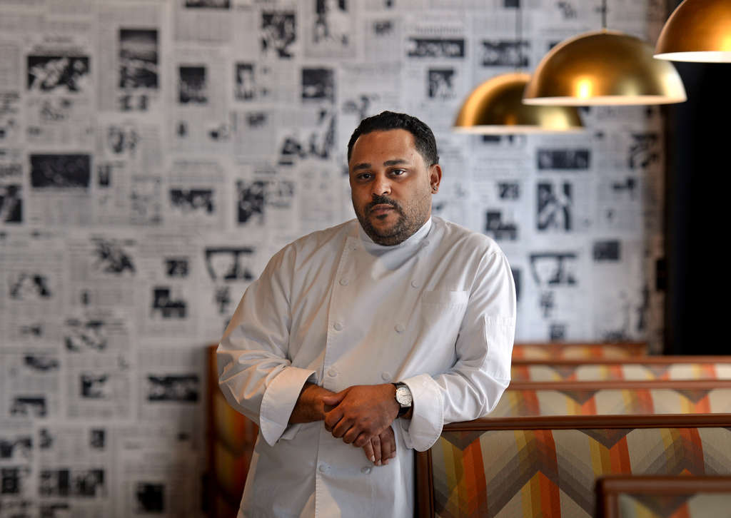 Chef and owner Kevin Sbraga in the dining room of Juniper Commons on South Broad Street. Old newspaper front pages, along with old album covers, cover the walls of the retro restaurant. TOM GRALISH / Staff Photographer