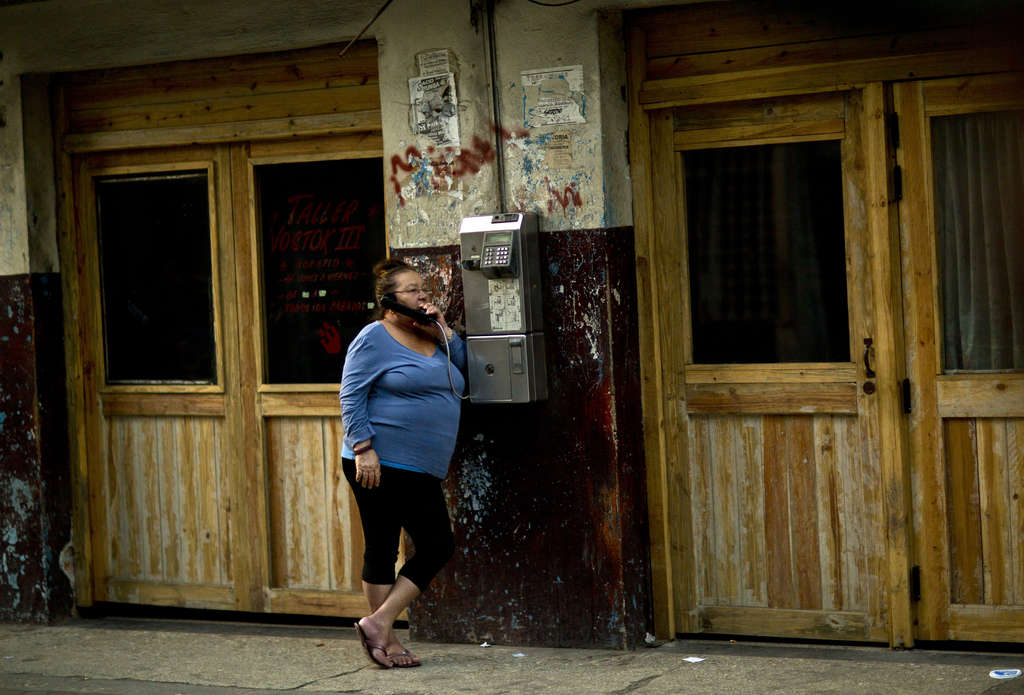 A woman uses a public phone in Havana. Infrastructure upgrades could be key to future ties.