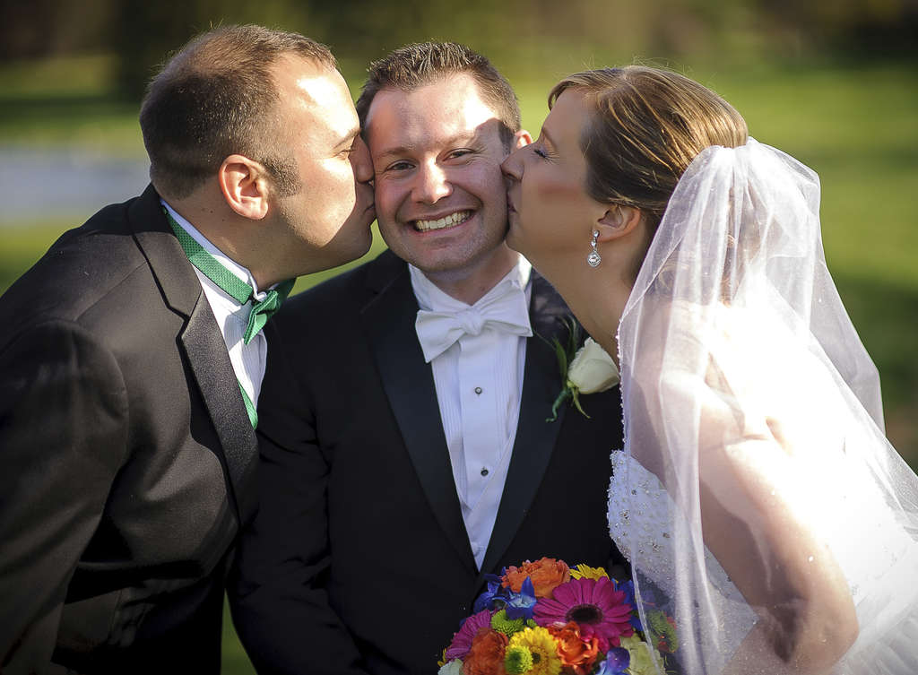 Bride Jennifer Voigt and best man Michael Amato, who introduced the couple, kiss groom Christopher Hoffer.