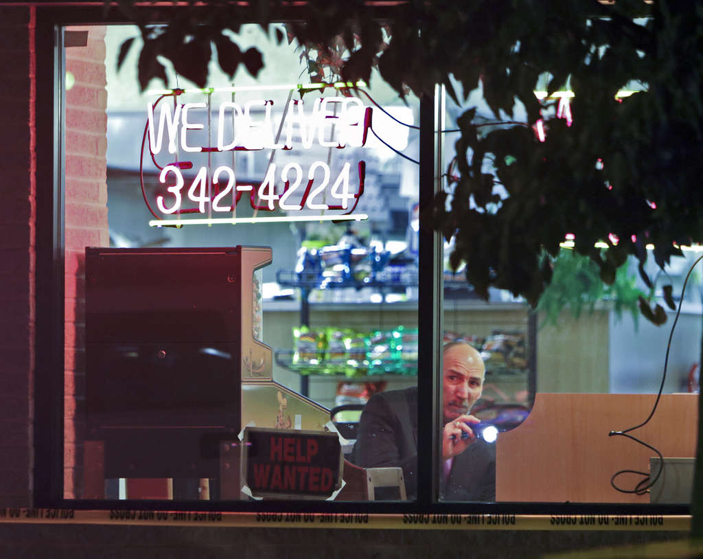 JOSEPH KACZMAREK/ FOR THE DAILY NEWS An investigator looks for evidence Thursday inside Rising Sun Pizza in Lawndale, where an off-duty detective shot and killed one of two men who attempted to rob the pizza shop.