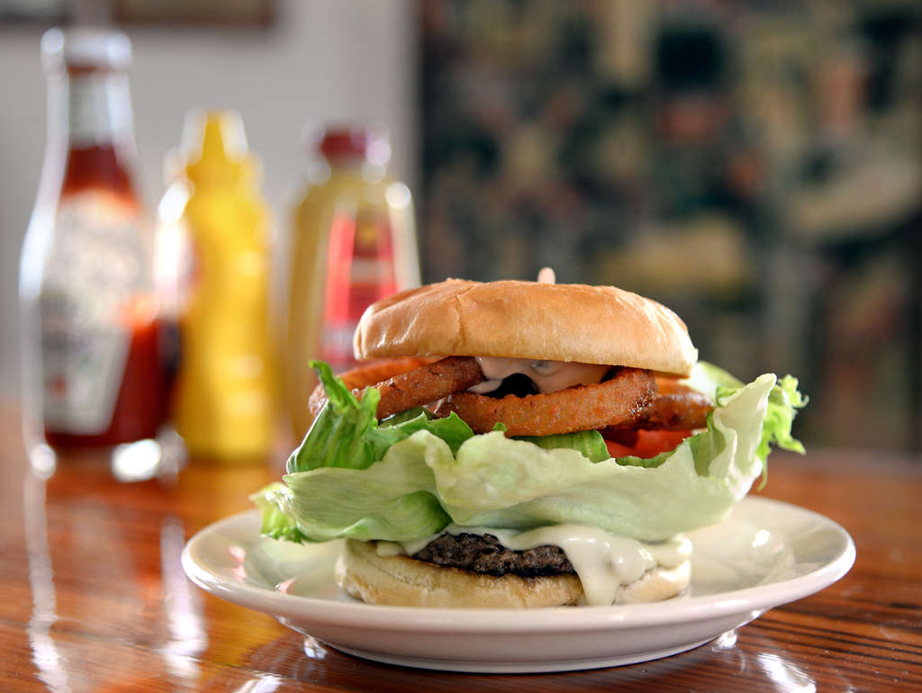 The Slam Burger, a cheeseburger with fried onion ring, lettuce, tomato, and Russian dressing, at the Holiday Snack Bar in Beach Haven. The freshly ground burgers, house-formed each morning and served over a griddled bun, are a flat-patty dream.