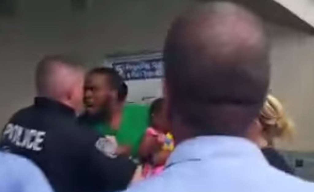 Screenshot from video shows man holding his daughter during confrontation with SEPTA police.