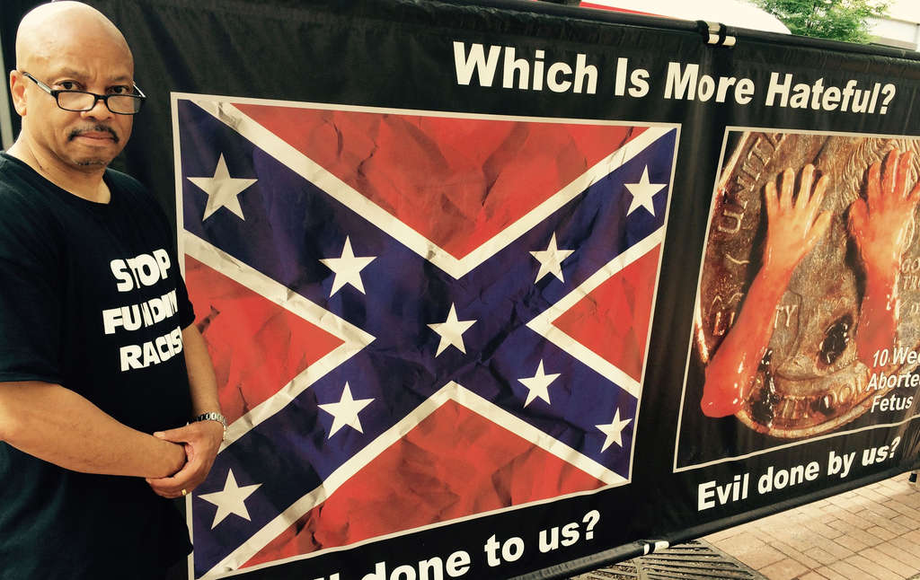 STU BYKOFSKY/DAILY NEWS STAFF The Rev. Clenard Childress with a Confederate flag poster, taunting the NAACP on its abortion-rights position.