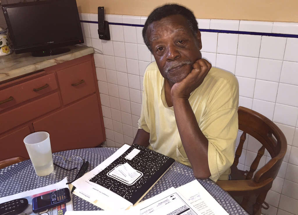 RONNIE POLANECZKY/DAILY NEWS STAFF Ron Walker reviews his unpaid medical bills in his West Philly kitchen. He could pay them tomorrow if the Sheriff´s Department would cut him the check he´s owed for the sale of a house he owned.