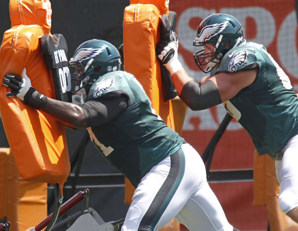 MICHAEL BRYANT / STAFF PHOTOGRAPHER Jason Peters, working with the blocking sled with Lane Johnson, says he took up yoga to help him get better in shape.