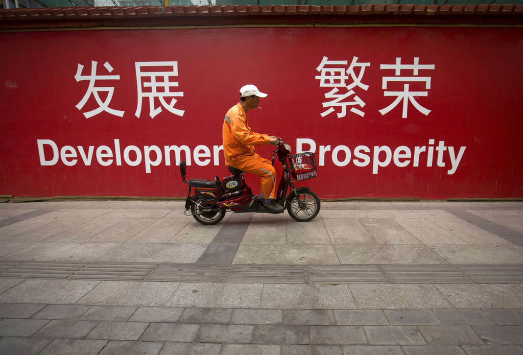 A man rides past banners with an upbeat message on a street in central Beijing.