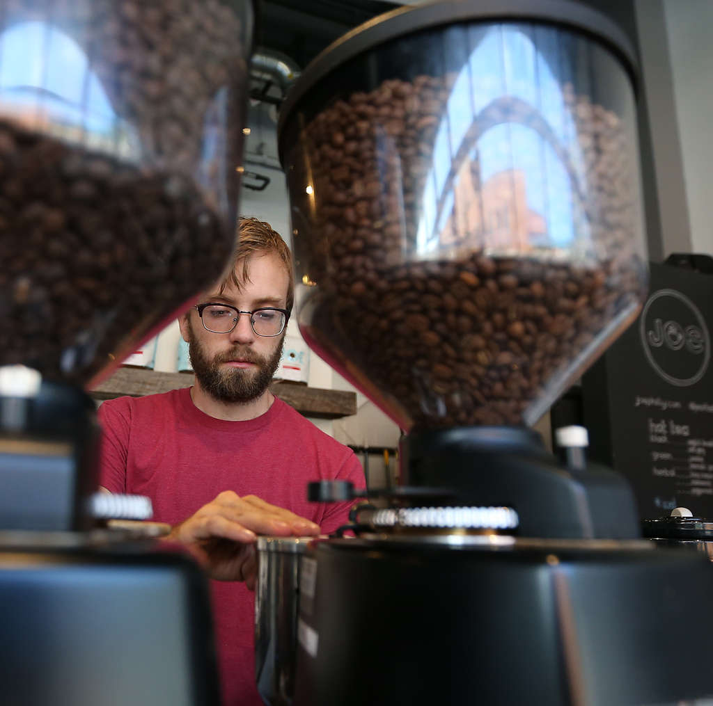 Barista David Thompson grinds coffee beans at Joe Coffee on the 3200 block of Chestnut Street in University City. The small chain received loans from Bond Street to open two outlets in Manhattan.