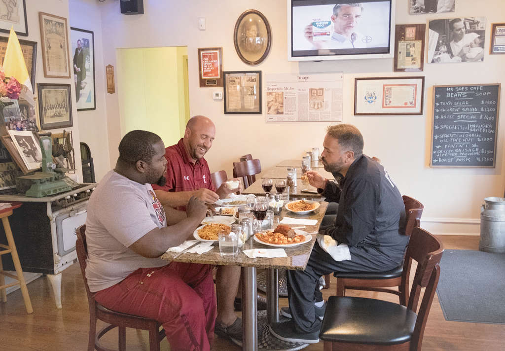 Temple football coach Matt Rhule (right) enjoys a ritual lunch on Thursday with Mike Wallace, a recruiting assistant (left), and linebackers coach Mike Siravo (center) at Mr. Joe´s Cafe in S. Philadelphia, in hope of continuing the team´s winning ways.