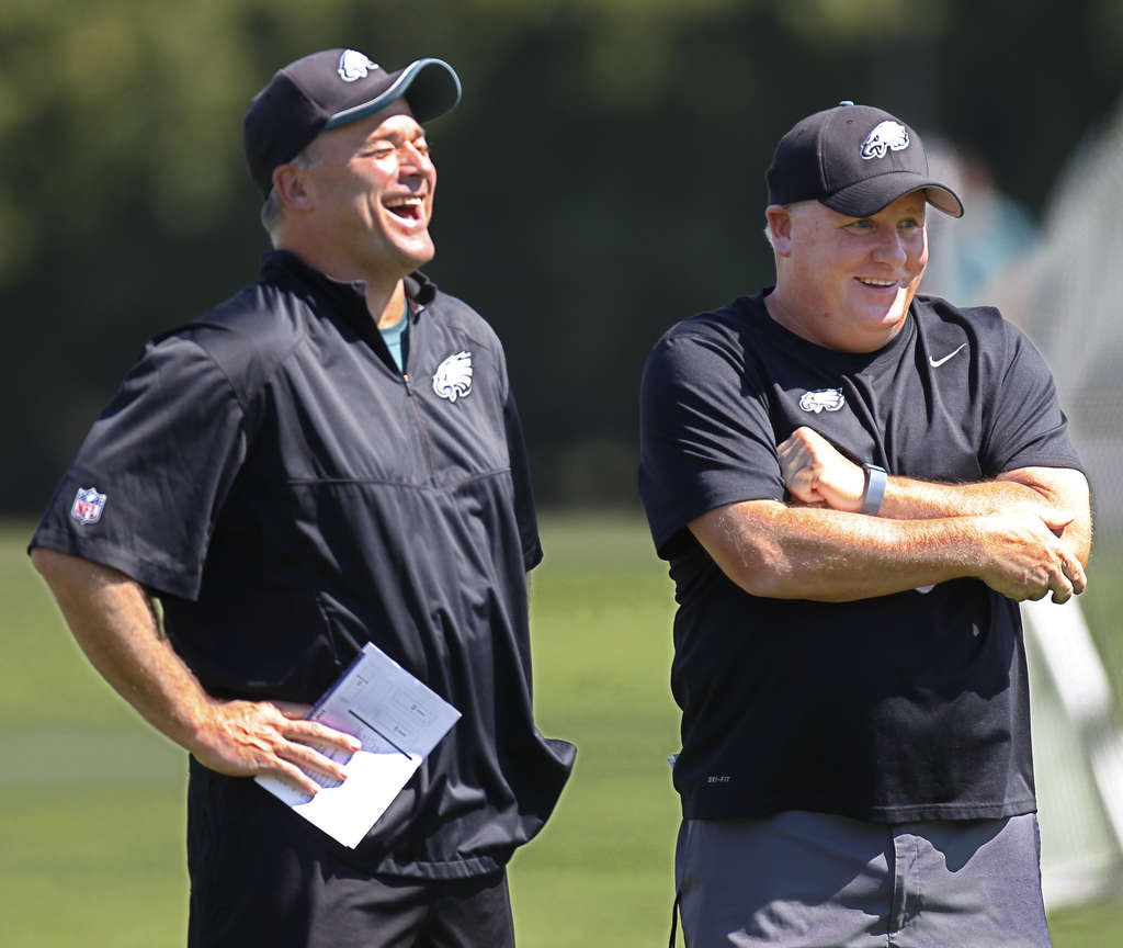 MICHAEL BRYANT / STAFF PHOTOGRAPHER Bill Davis, with Chip Kelly in a light moment at practice, says that the season opener is a starting point, but that the Eagles should improve this week.
