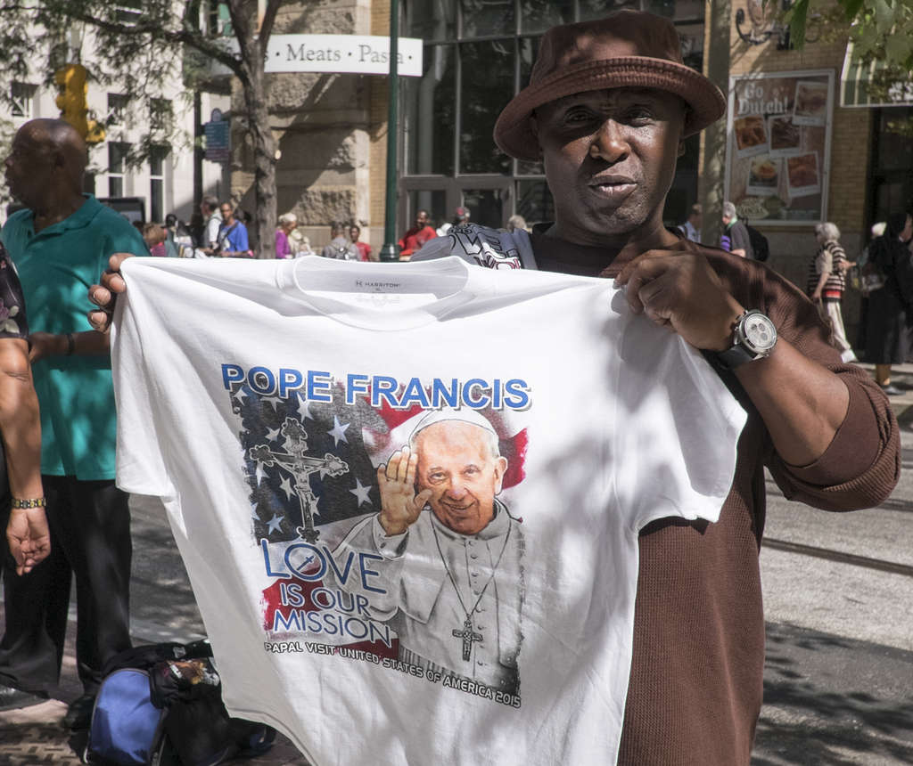 ED HILLE / STAFF PHOTOGRAPHERT-Party Hey, it´s a big event and people are going to want souvenirs, right? The hawkers were out yesterday in Center City a couple days ahead of the pope´s arrival, showing off all kinds of papal mementoes. Here, a Pope Francis T-shirt does the trick.