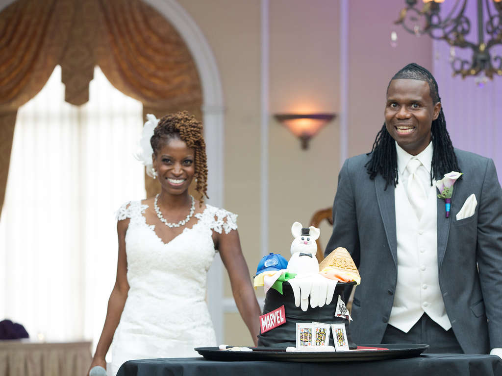 Newlyweds Zupenda Davis and Randy Shine, with the groom´s cake, showcasing his love of magic, his alma mater Penn State, his fraternity, WWE Wresting, and comic books.