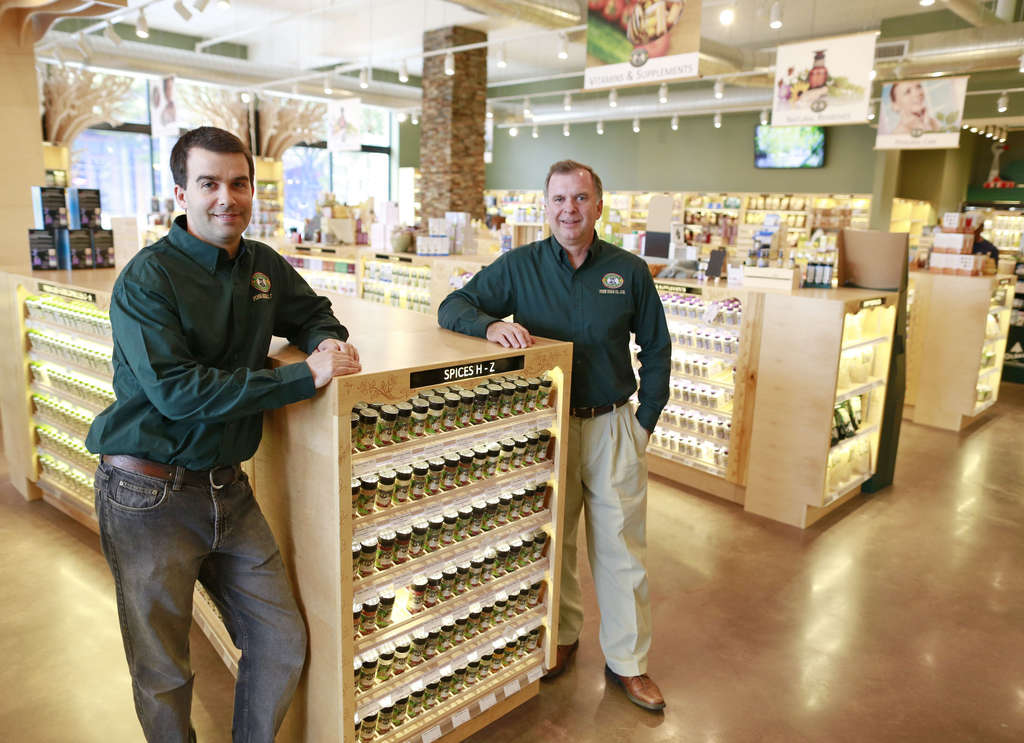 William Betz III (left) and William Betz Jr. in the reopened Penn Herb Co. The new building at Second and Green Streets features information kiosks, grocery items and 14 apartments.