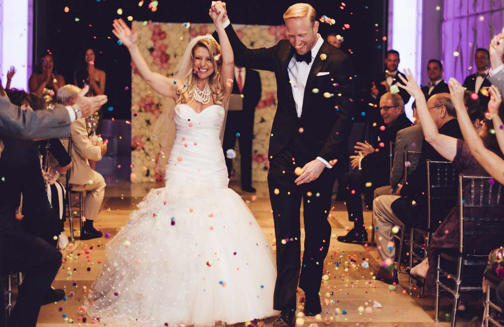 Newlyweds Kelly Magnussen and Frank Tagye are pelted with pom-poms by their friends, family, and other wedding guests.