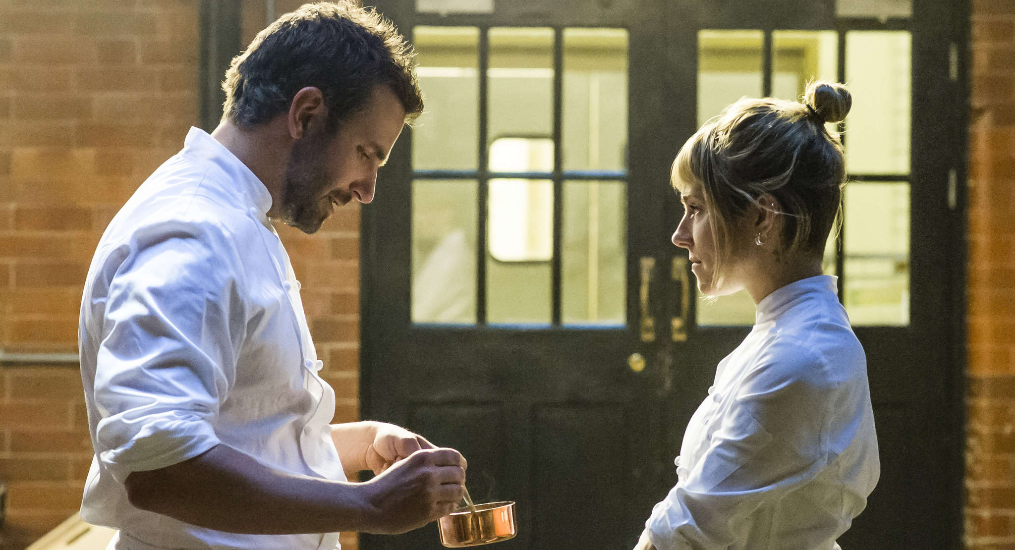 "Bradley Cooper is Adam, a chef in search of redemption, and Sienna Miller is Helene in ""Burnt."""
