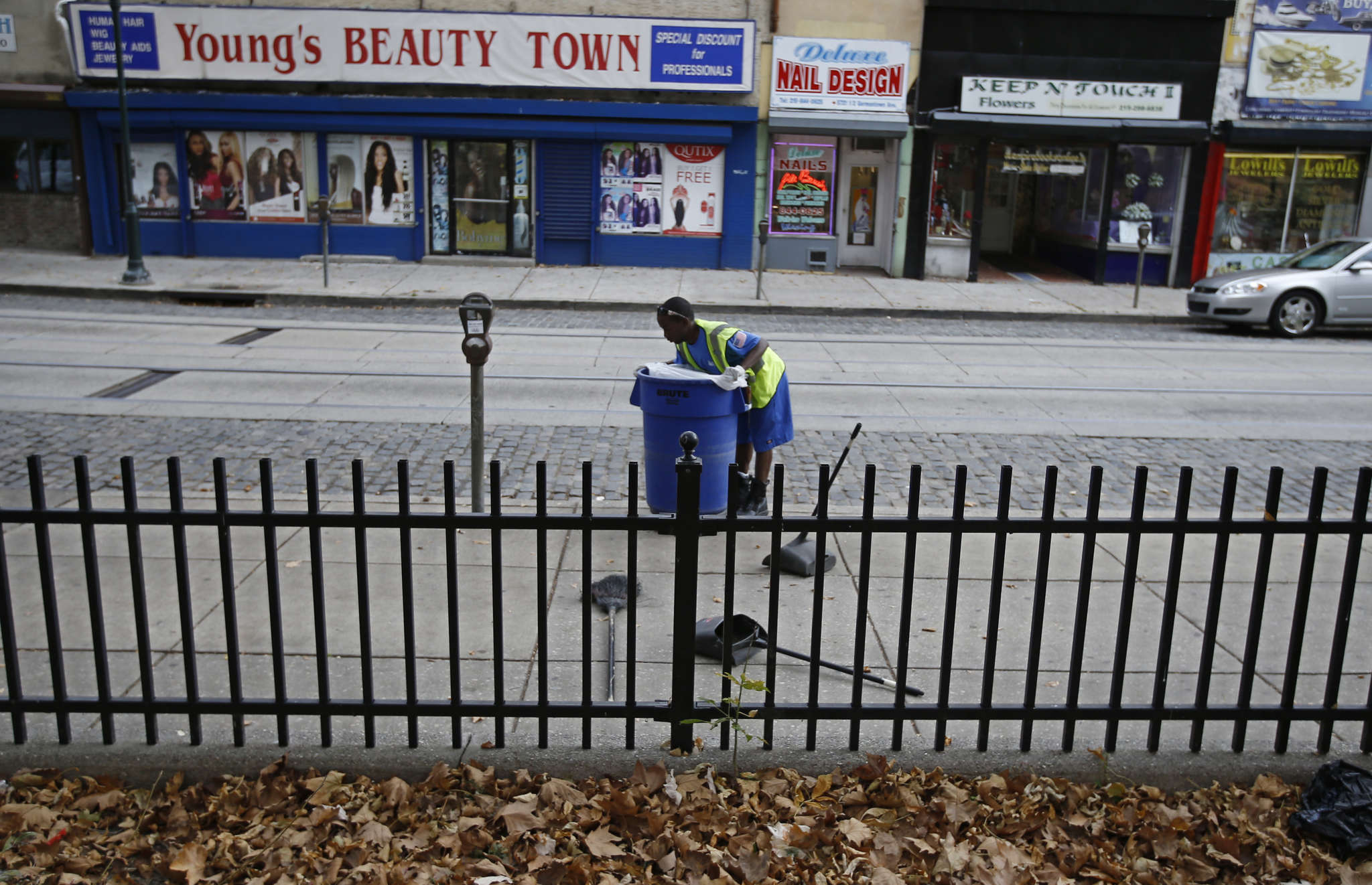 A worker cleans the sidewalk on Germantown Avenue outside Vernon Park. The city invested $1.2 million in cleaning up the seedy park, but the nearby shopping district has yet to develop.