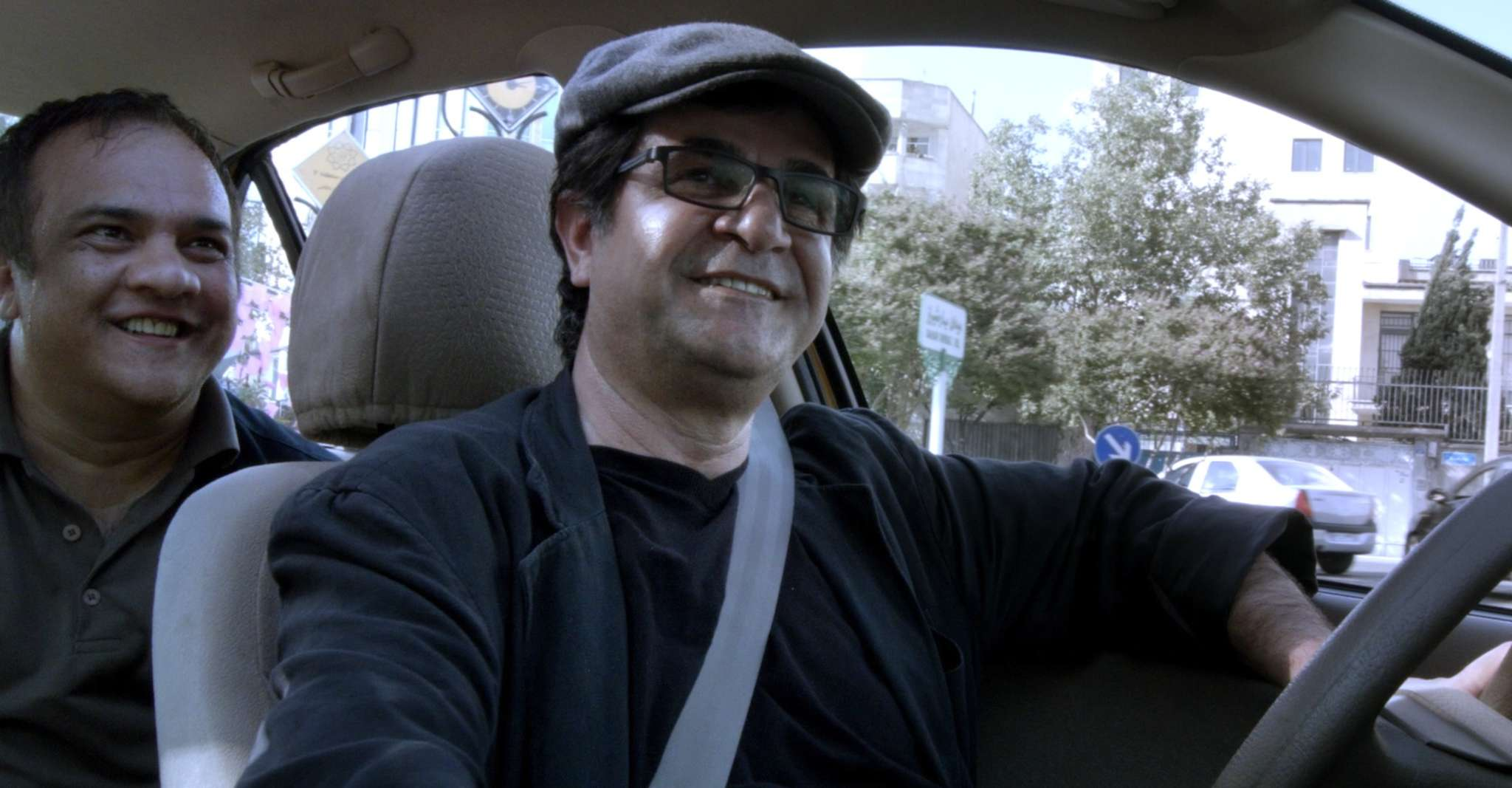 "Iranian film director Jafar Panahi (right), banned by the government from making movies for 20 years, recorded passengers as he drove a cab in Tehran - making ""Jafar Panahi´s Taxi."""