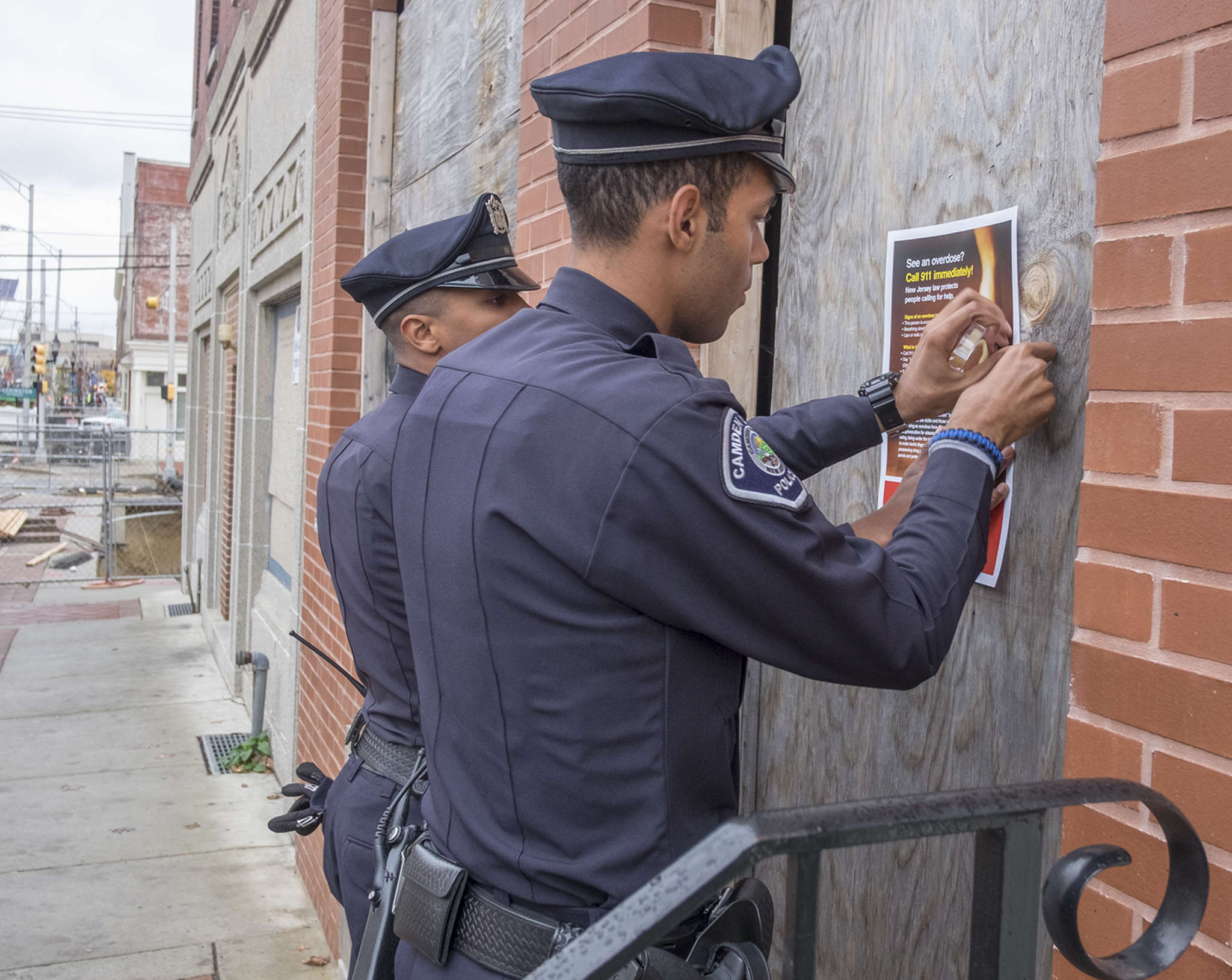 Camden County Officers Vidal Rivera (left) and Tyrell Bagby post information on a boarded-up building on Broadway. They were part of the outreach effort. ED HILLE / Staff Photographer
