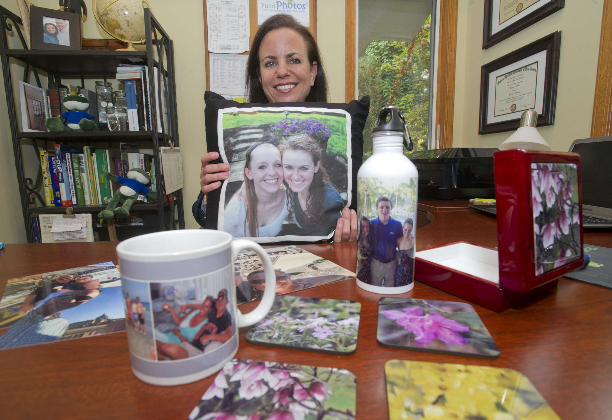 Amy Wiker, owner of the Mount Laurel-based FundPhotos, seen here in her Medford Lakes home, shows off some of their product including photo prints and photos printed on mugs, coasters, water bottles, and pillows.  (Avi Steinhardt/ For the Philadelphia Inquirer)