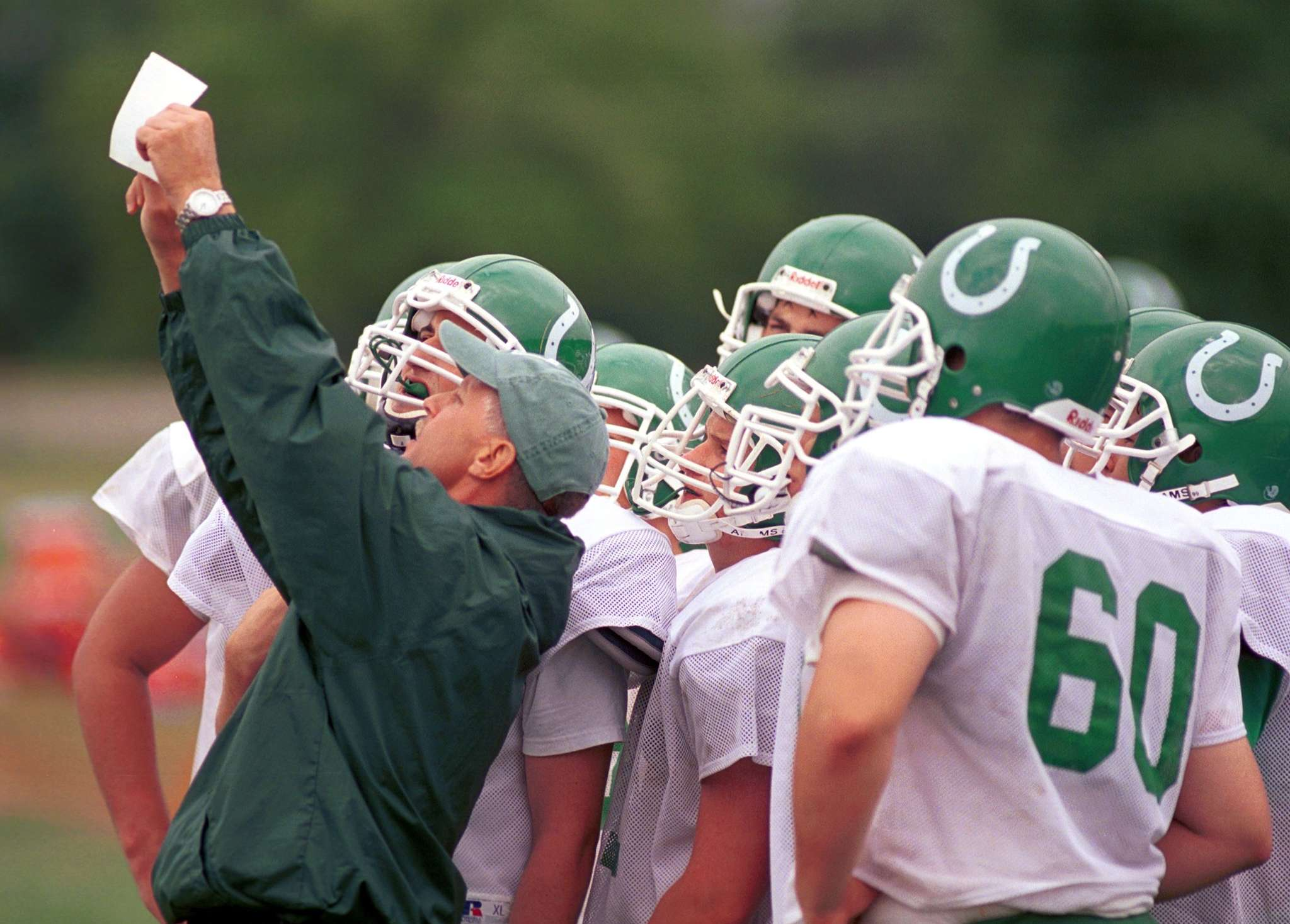 Mainland coach Bob Coffey diagrams a play in the huddle for his Mustangs in 2002. Coffey´s team won five sectional titles, one of which was controversially erased. He was also there for his team and school after a 2011 car accident that took the lives of four players.