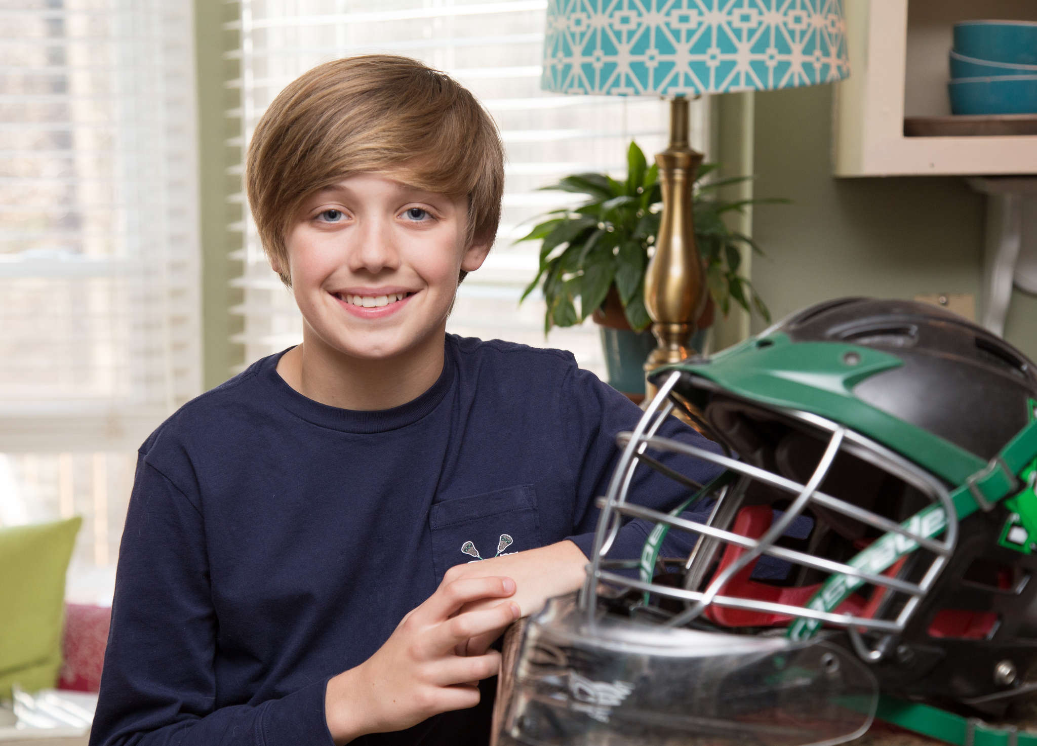 Braeden Lange, 12, at home with the lacrosse helmet he received from his mentor.
