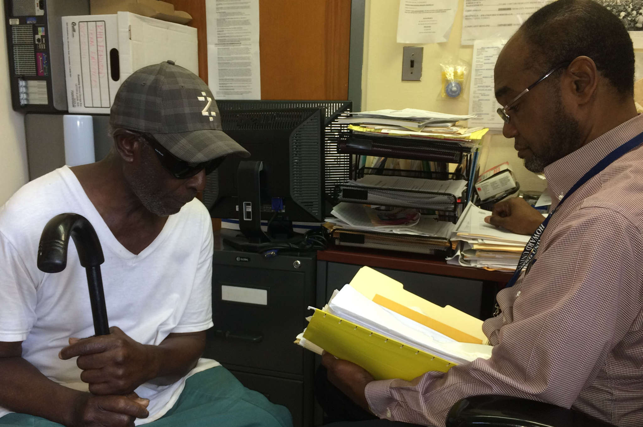 Julius Jackson (right), director of the Fernwood emergency-housing shelter, reviews Samuel Foster´s file. STU BYKOFSKY/DAILY NEWS STAFF