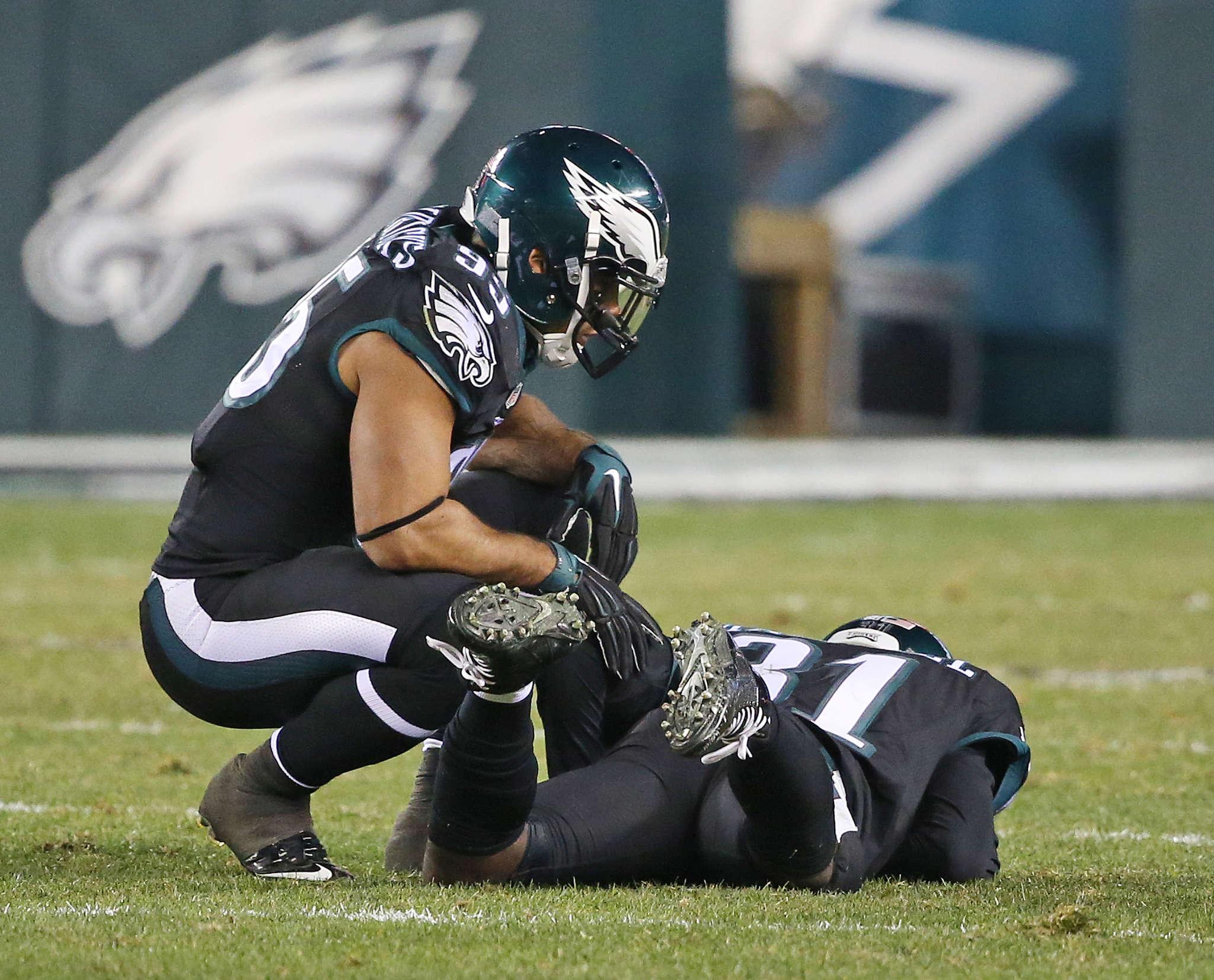 Eagles linebacker Mychal Kendricks checks on injured cornerback Byron Maxwell. DAVID MAIALETTI /STAFF PHOTOGRAPHER