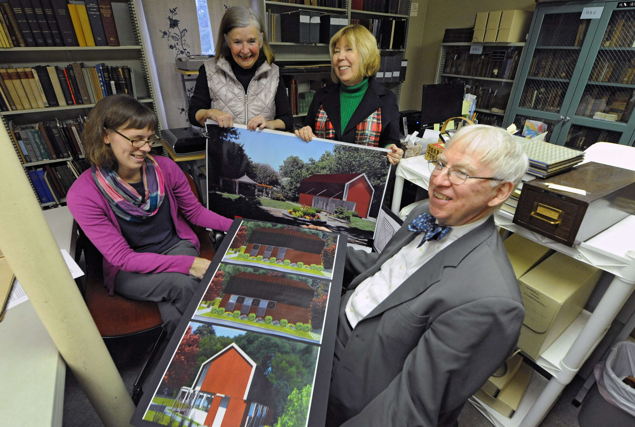 Showing off the architectural renderings of the proposed Archive Center for the Historical Society of Haddonfield are (from left) librarian and archivist Dana Dorman, former librarian Kathy Tassini, president Carol Smith, and retired Haddonfield librarian and library committee chair Doug Rauschenberger.