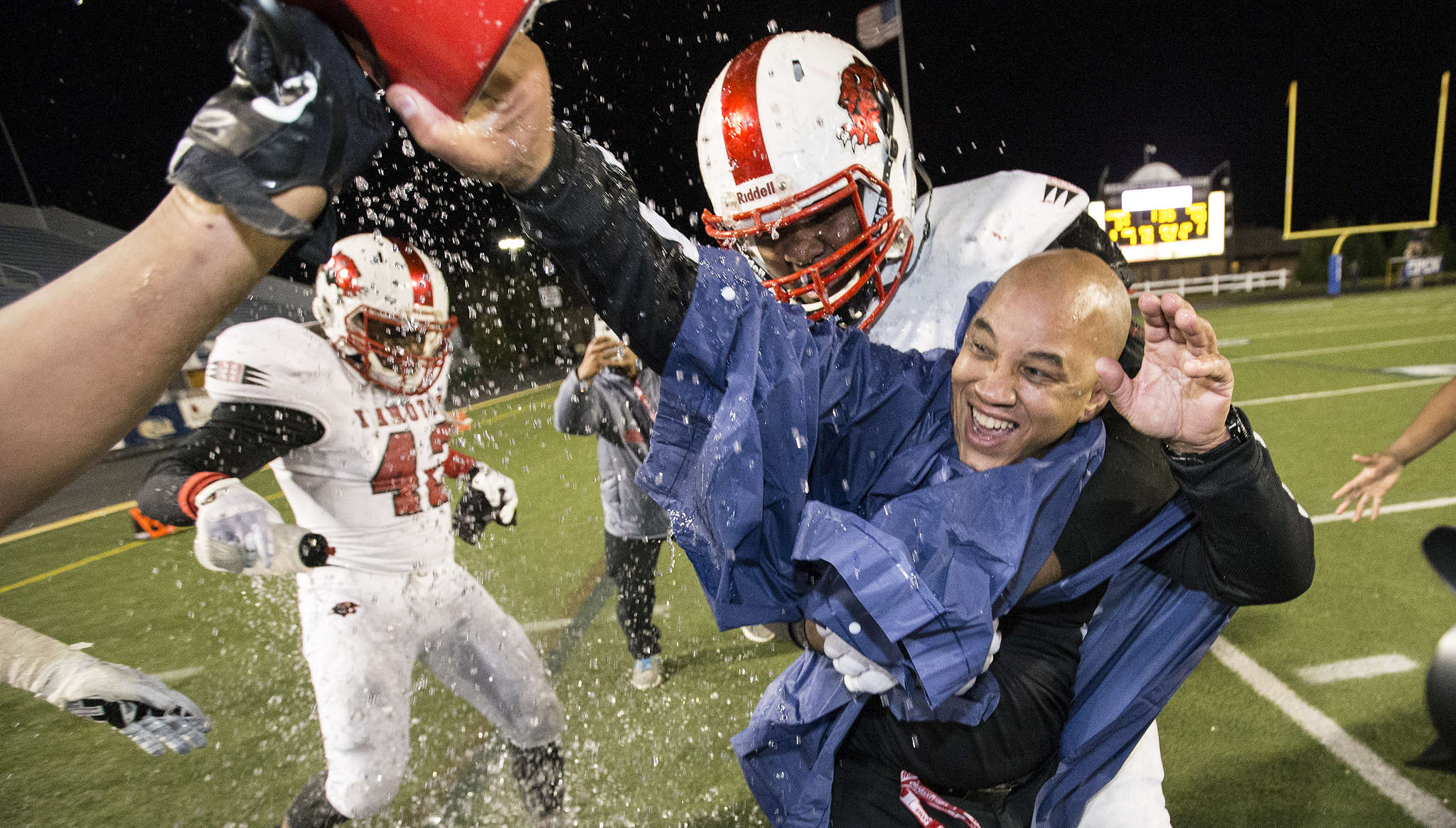 Imhotep head coach Albie Crosby gets the requisite victory shower in the final minutes of the Panthers´ 40-3 victory over Erie Cathedral Prep in the Class 3A state championship game Dec. 19. Crosby was named state 3A coach of the year by Pa. football writers.