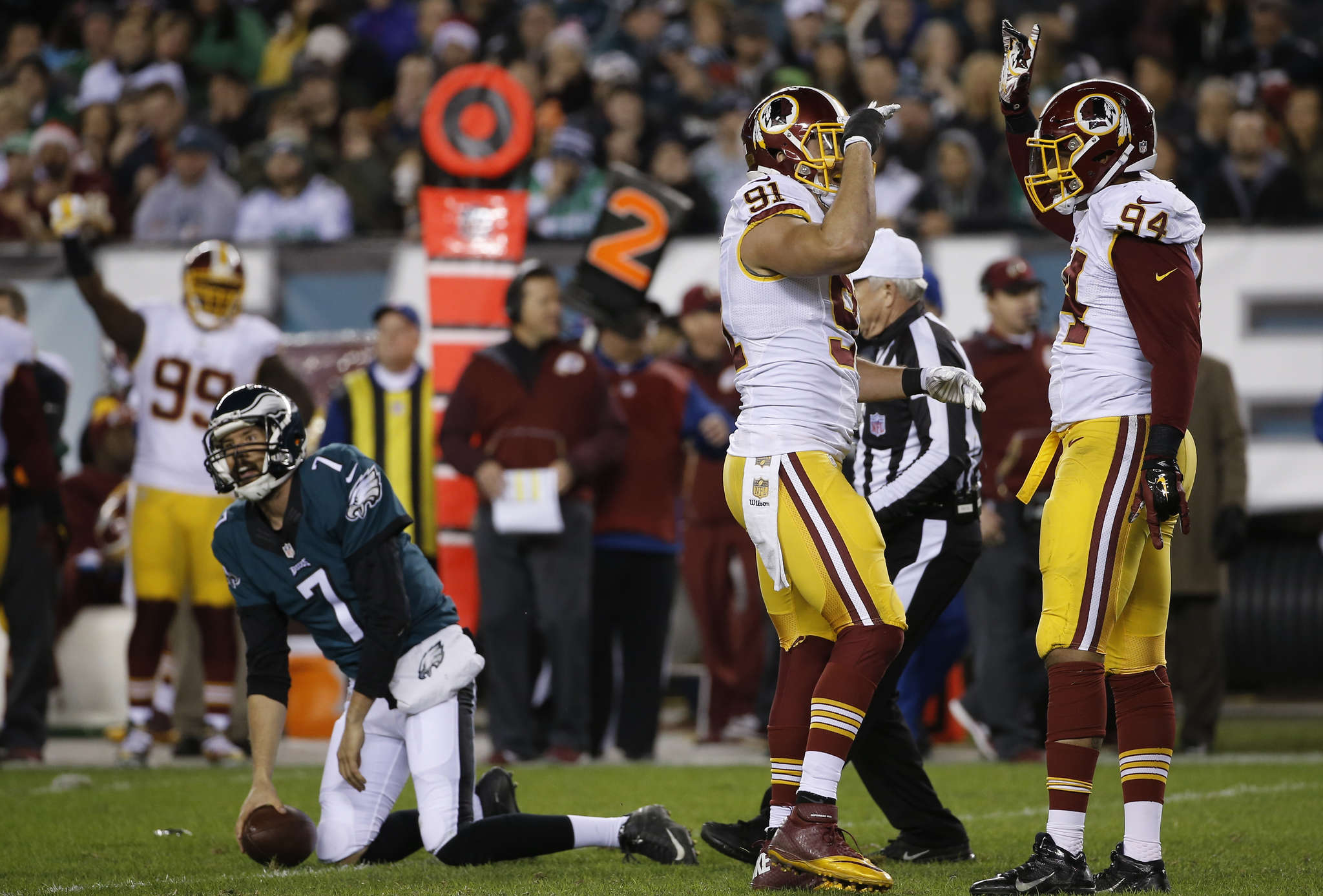 Sam Bradford gets up slowly after being sacked as Redskins defenders Ryan Kerrigan (left) and Preston Smith exchange high-fives. MICHAEL PEREZ / AP