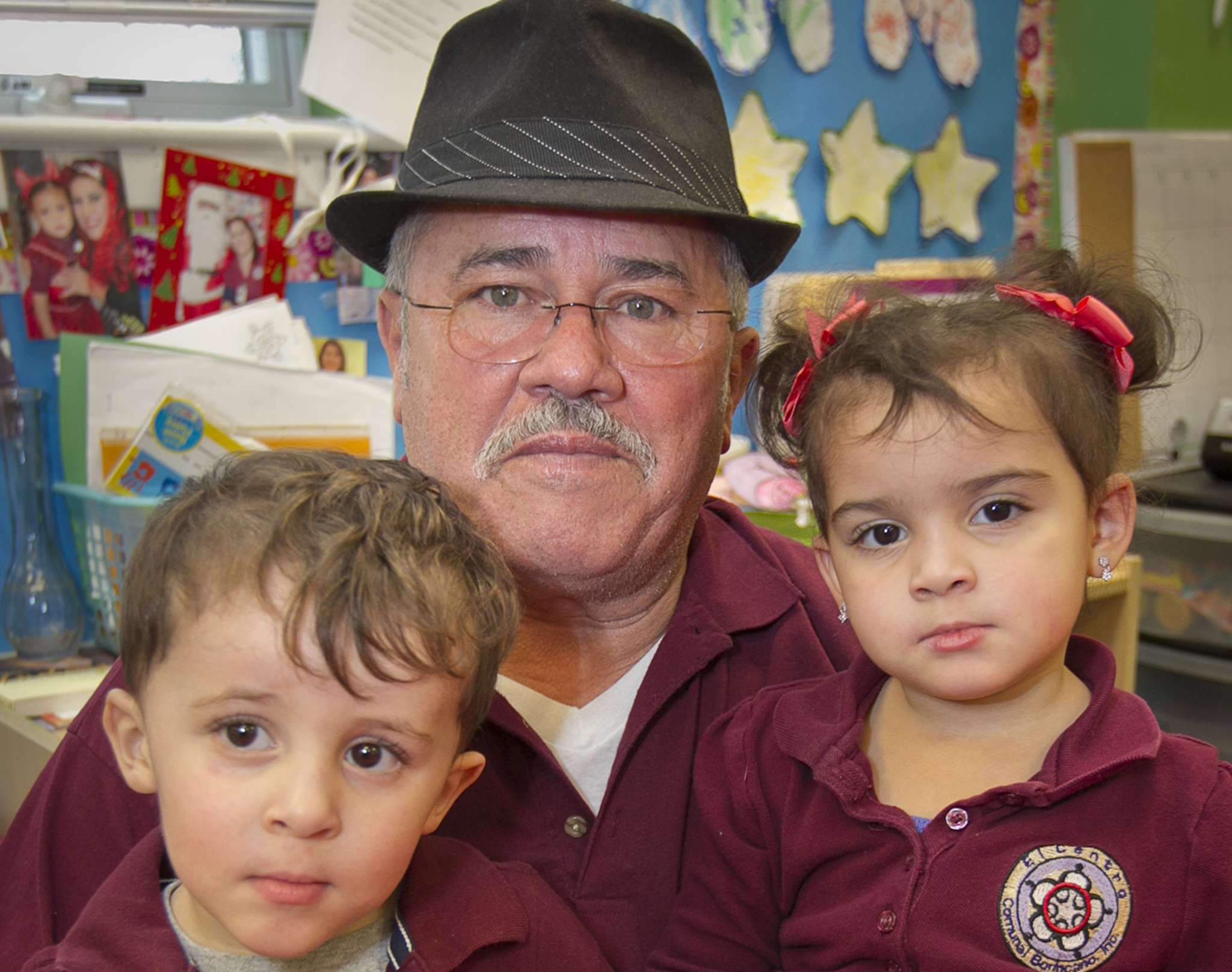 "At El Centro, a Camden day care , Foster Grandparents volunteer Andres Plaza holds his grandchildren Nelson and Nelania Hidalgo. Other children, too, ""hug me and play with my hat,"" he says. ALEJANDRO A. ALVAREZ / Staff Photographer"