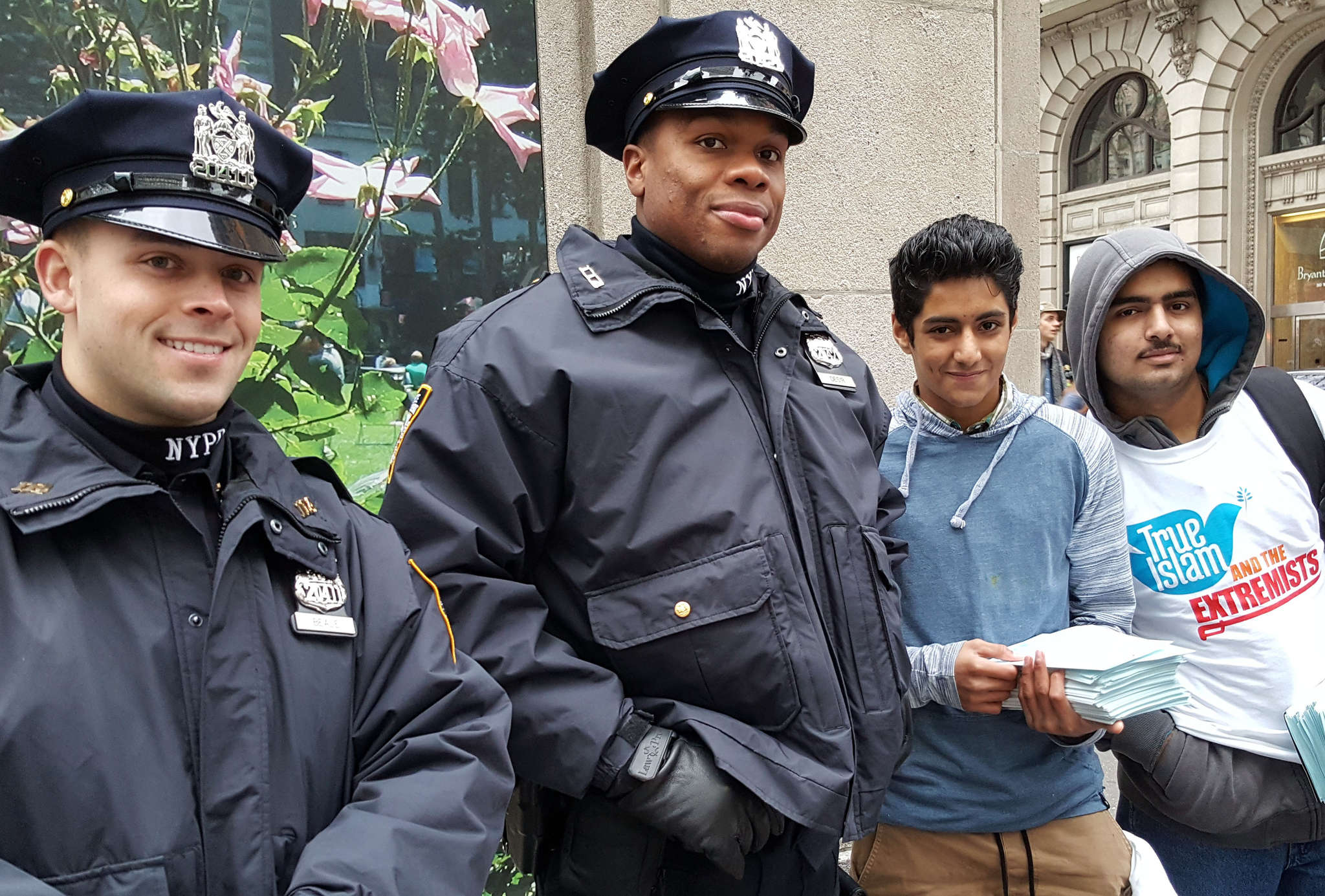 New York City cops, with members of the Ahmadiyya Muslim sect, who are distributing literature opposing Islamic extremism.