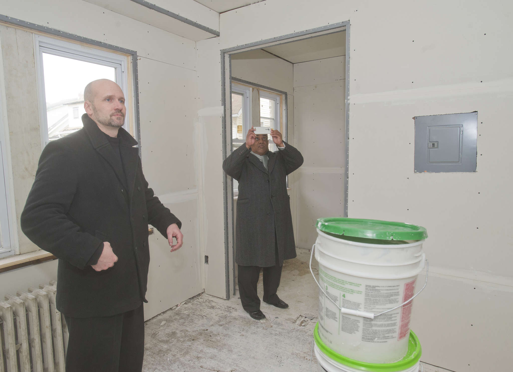 Oaklyn Mayor Bob Forbes (left) and Gino Lewis, director of housing for the Camden County Improvement Authority, look at an apartment being rehabilitated.