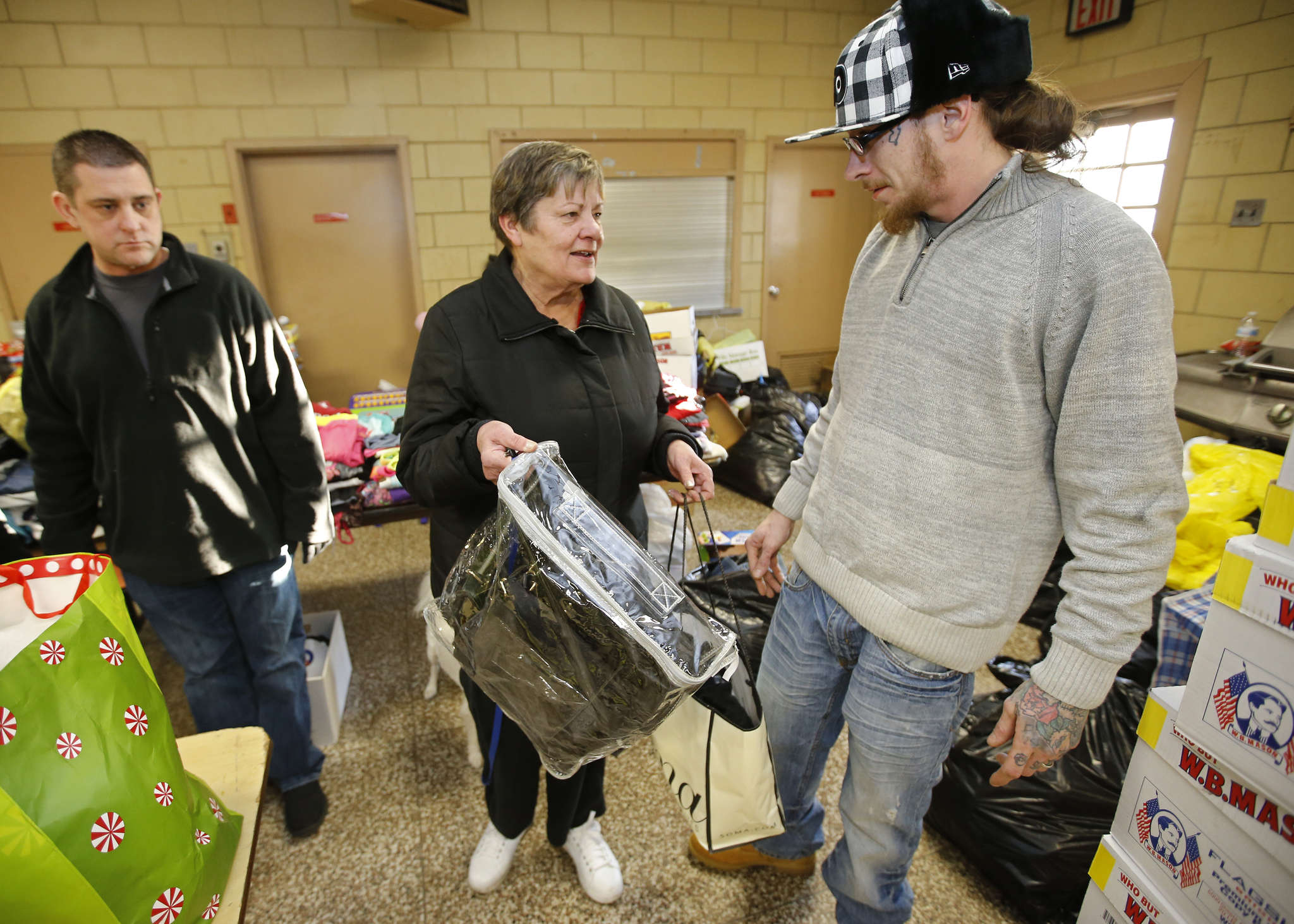Christine Dragon , who was burned out of her Burlington City home, received enough help to make her own donation. She was at the drop-off point with volunteers Michael Lloyd (left) and Steven Whitfield. MICHAEL BRYANT / Staff Photographer