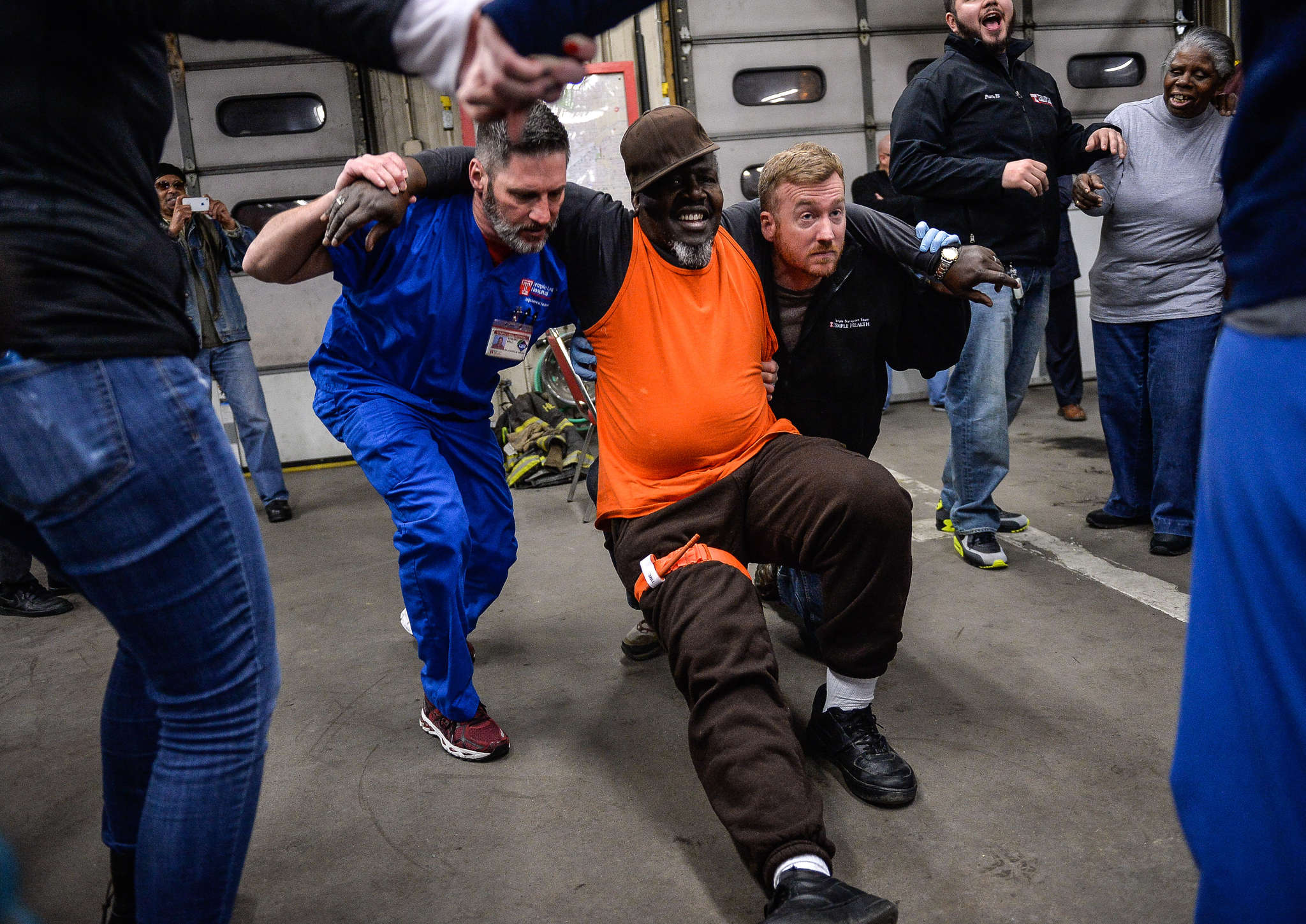 "Edward Bell (left) and Tim Bryan carry Norman Wooten during a ""Fighting Chance"" training event at Ladder 12 in North Philly."