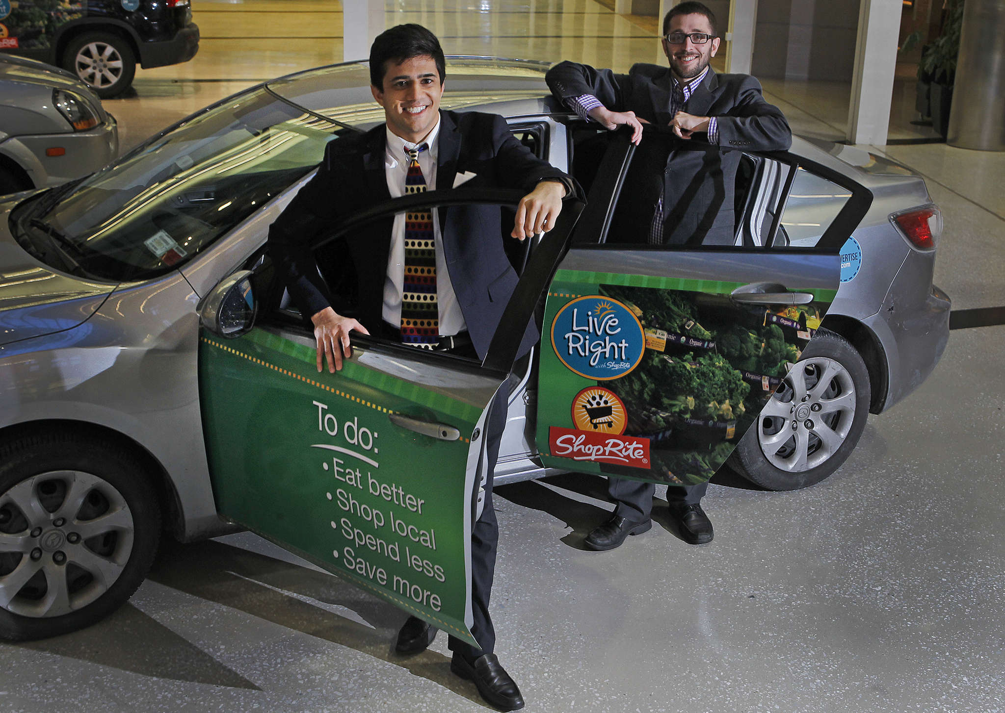 Carvertise cofounders Mac Nagaswami (left) and Greg Star with a wrapped vehicle at company headquarters in Wilmington.