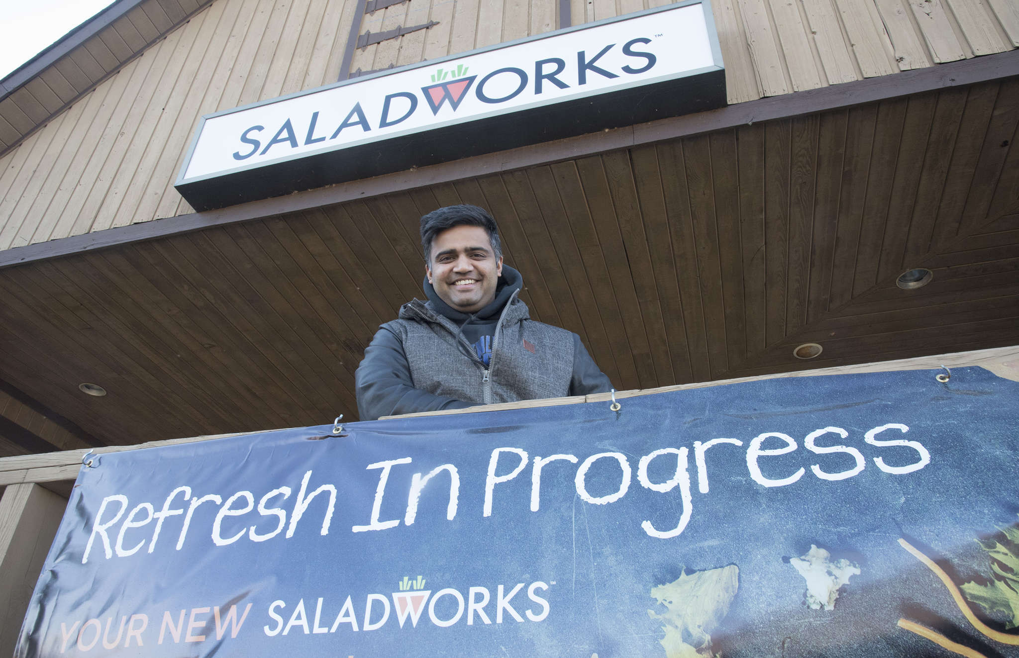 """Nish Patel, a Saladworks franchisee, looks out from his business in Newtown. The renovation will include adding a WiFi bar. """"This is what the new generation is attracted to,"""" Patel said."""