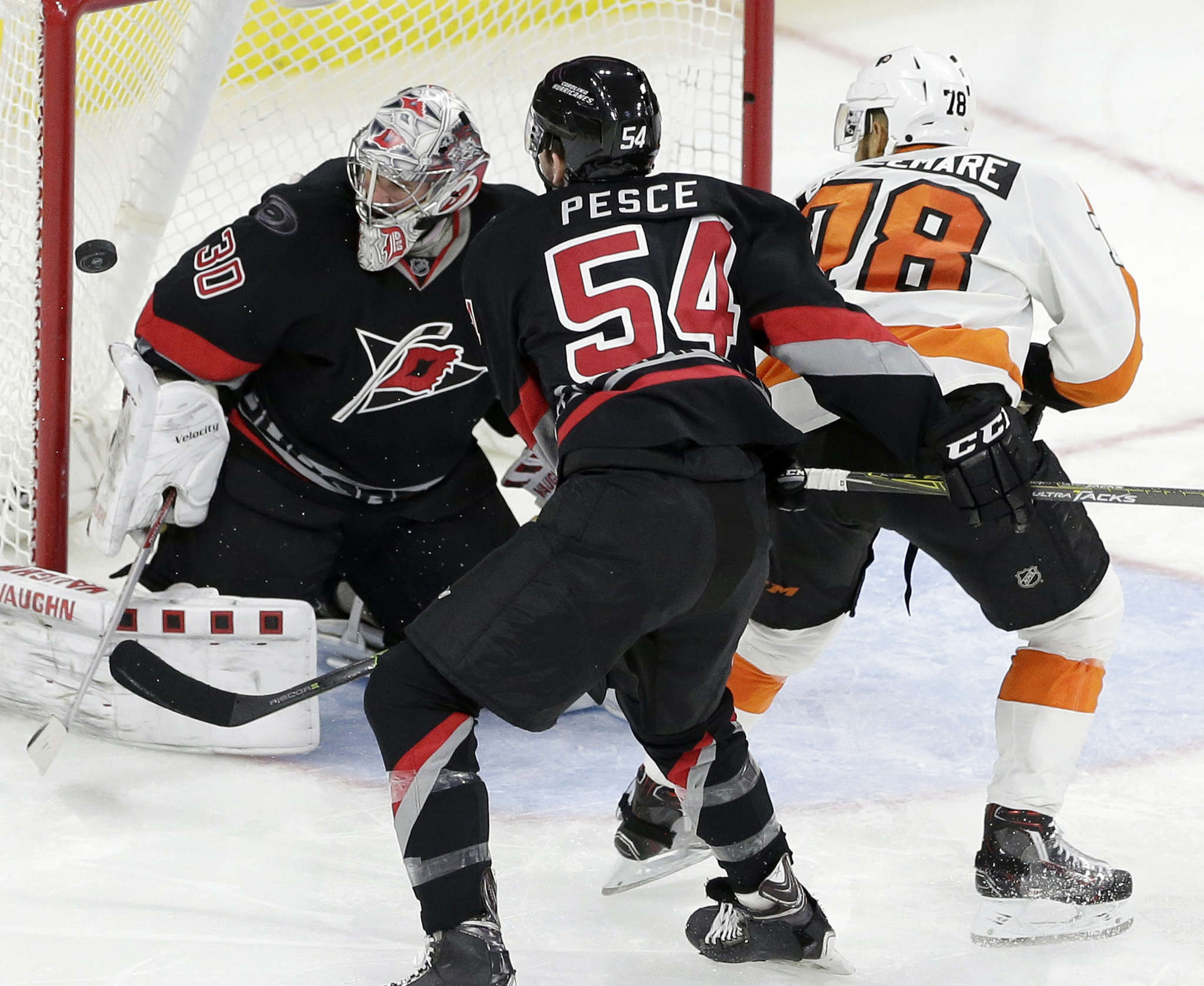 Hurricanes goalie Cam Ward stopped 36 Flyers shots on Tuesday, including this one with Pierre-Edouard Bellemare lurking. ASSOCIATED PRESS