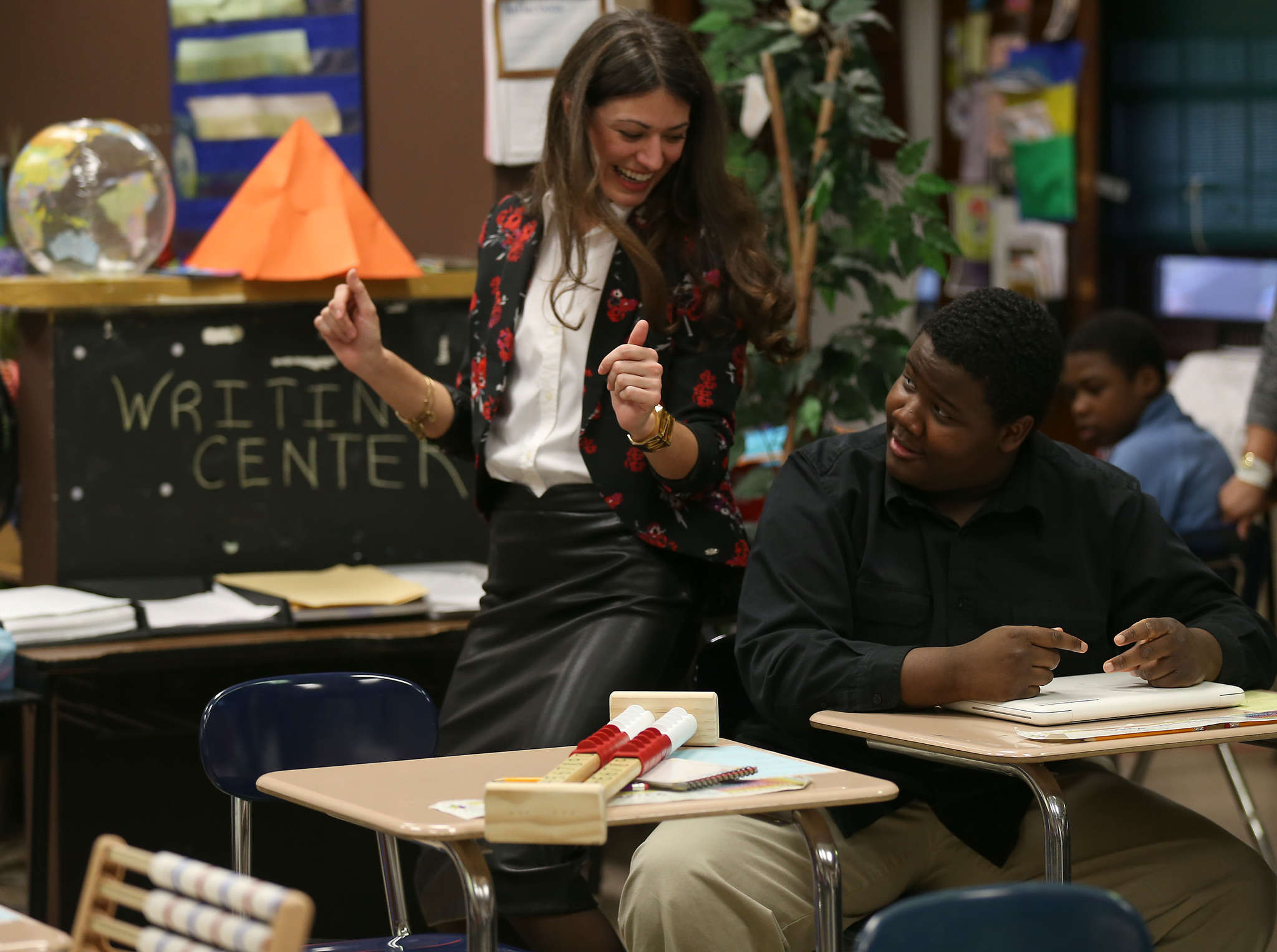 Michele McKeone celebrates a correct answer with Hassan Kone at Tilden Middle School in Philadelphia. McKeone´s company, Autism Expressed, which uses technology to teach students with disabilities, won a grant from the Corzo Center.