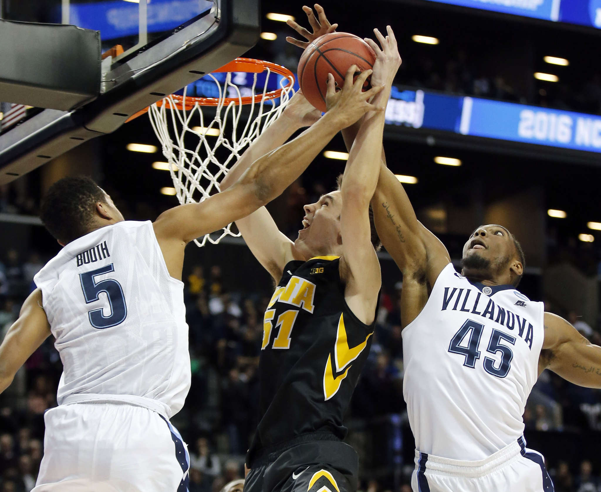 Villanova´s Phil Booth (left) and Darryl Reynolds sandwich Iowa´s Nicholas Baer in the first half.