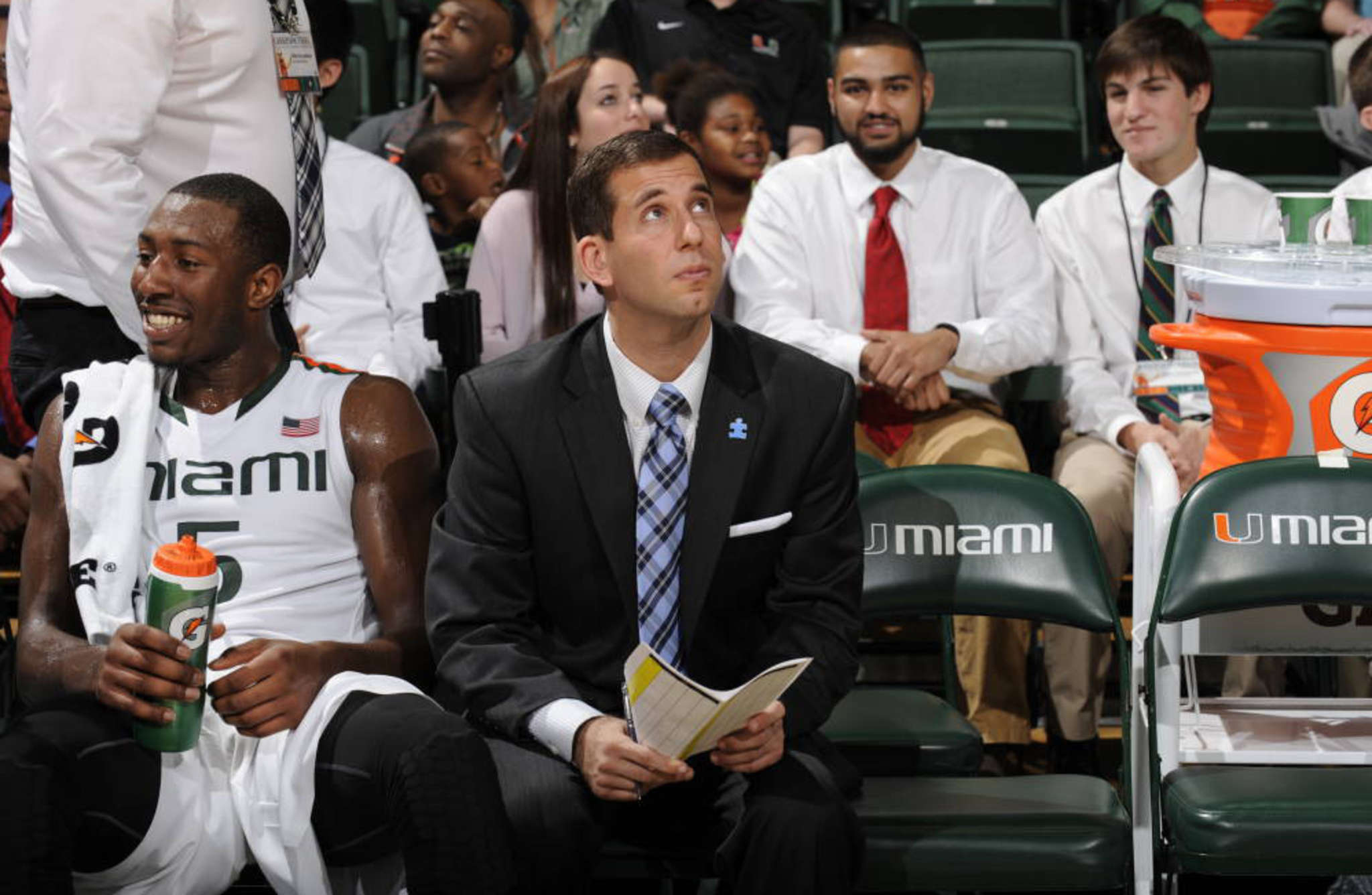 Miami assistant Adam Fisher on bench with guard Davon Reed. HURRICANESPORTS.COM