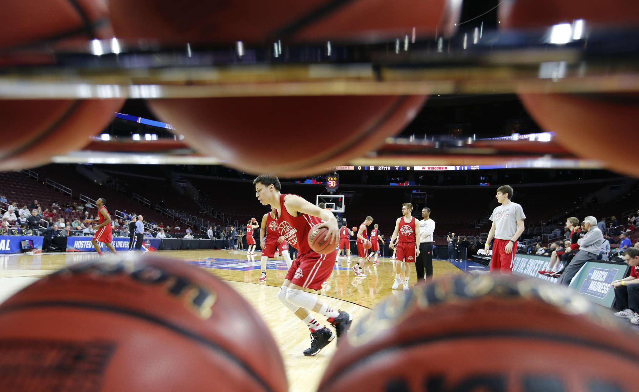 Viewed through a rack of basketballs,Wisconsin´s Bronson Koenig goes through drills. CHARLES FOX /Staff Photographer