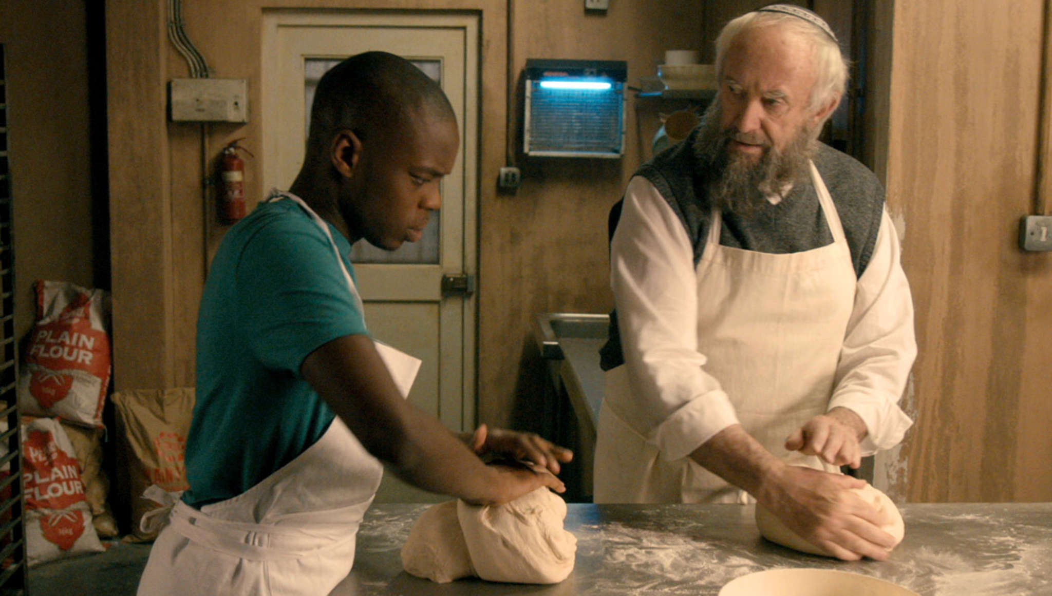 "Jonathan Pryce owns a Kosher bakery in ""Dough,"" with Jerome Holder as his apprentice. Menemsha Films"