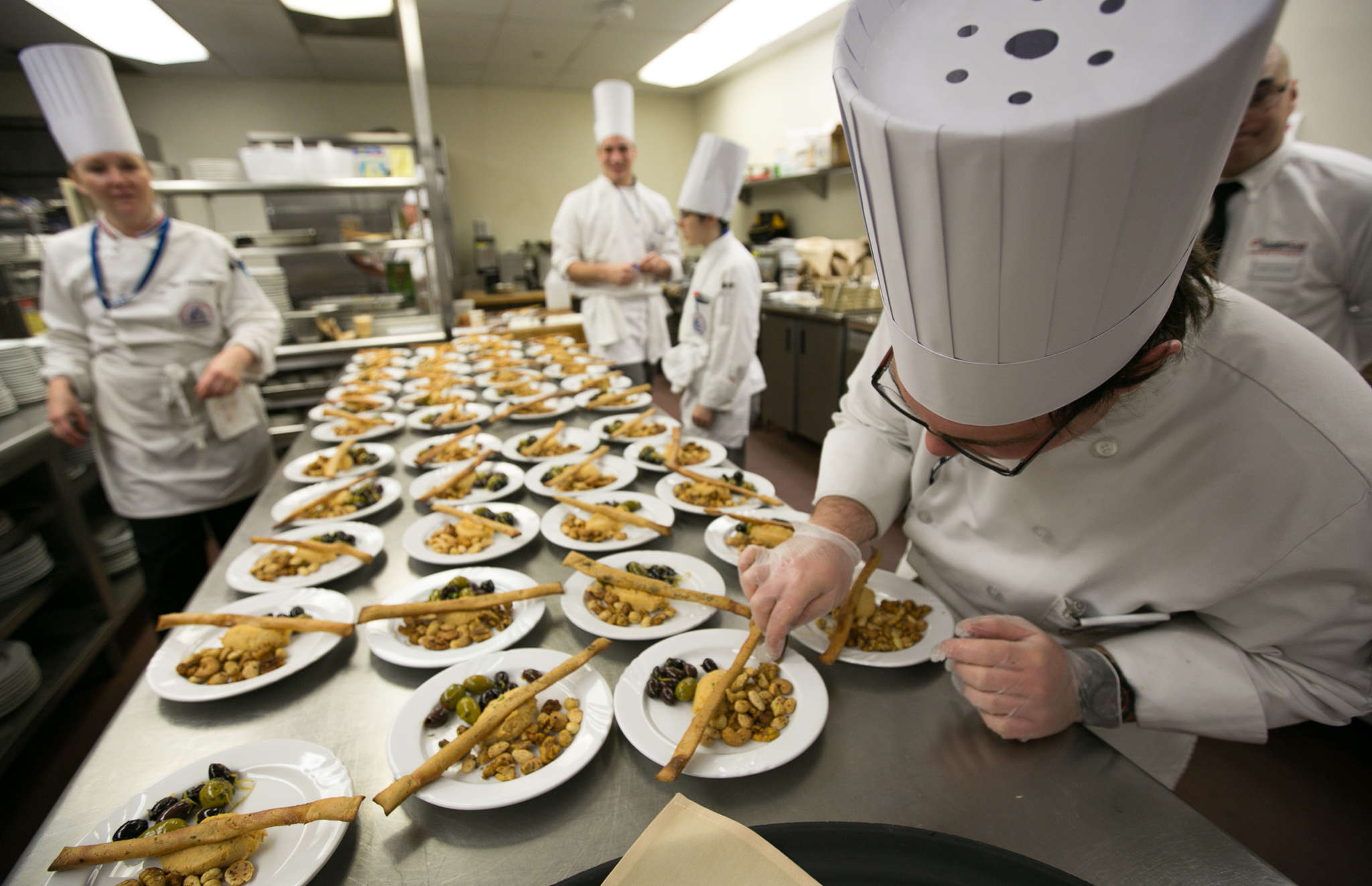 Peter Sroczynski, an Academy of Culinary Arts student, prepares plates for the springtime vegan dinner.