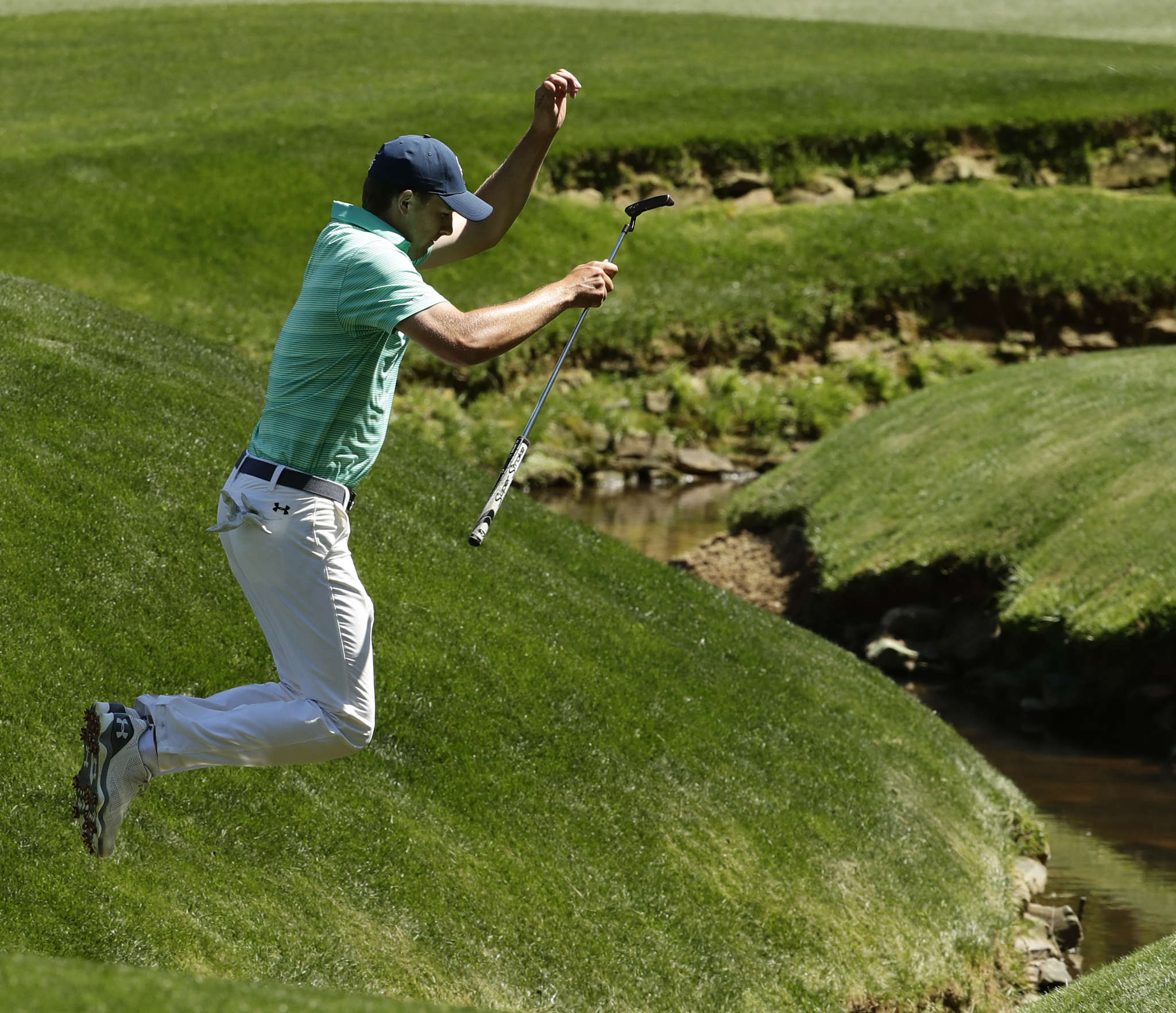 Jordan Spieth, jumping over a creek during a practice round for the Masters, has never really been in a tough battle with Tiger Woods. Associated Press