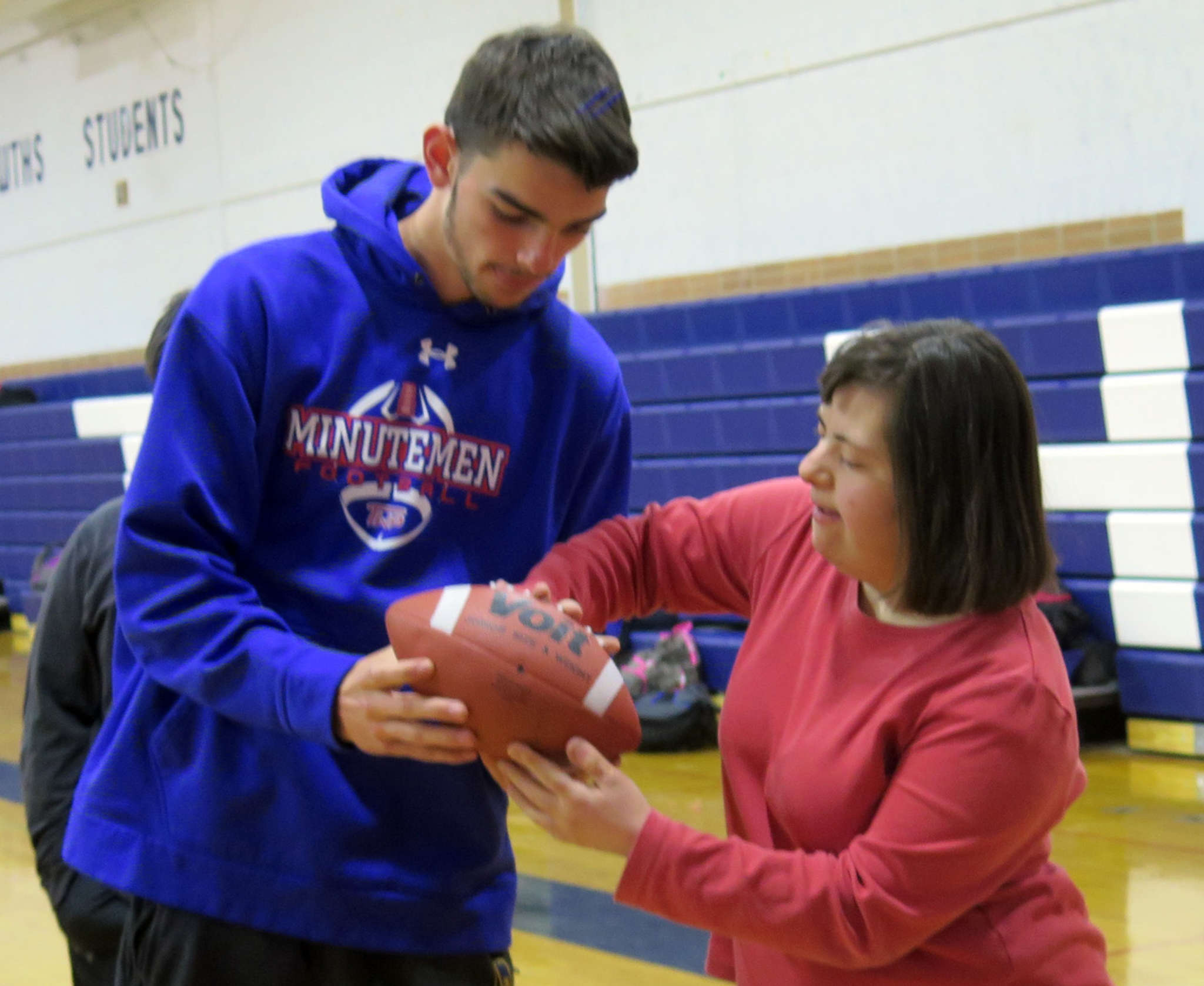Washington Township quarterback Mike Piperno shows Michelle Iacone the right way to grip a football when throwing a pass at a Project Unify clinic. MATT PESYNA