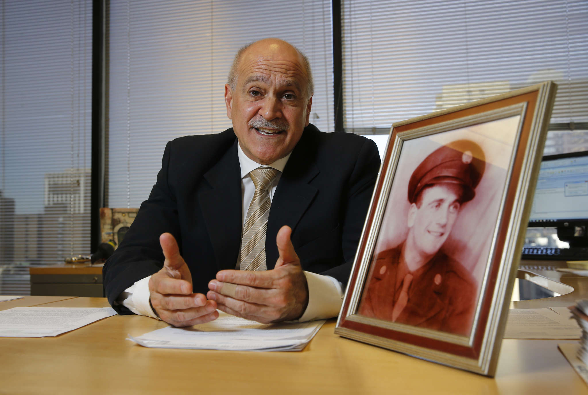 Skip Di Massa with a photo of his father, Rudolph. His background came in handy with a recent group of clients . MICHAEL BRYANT / Staff