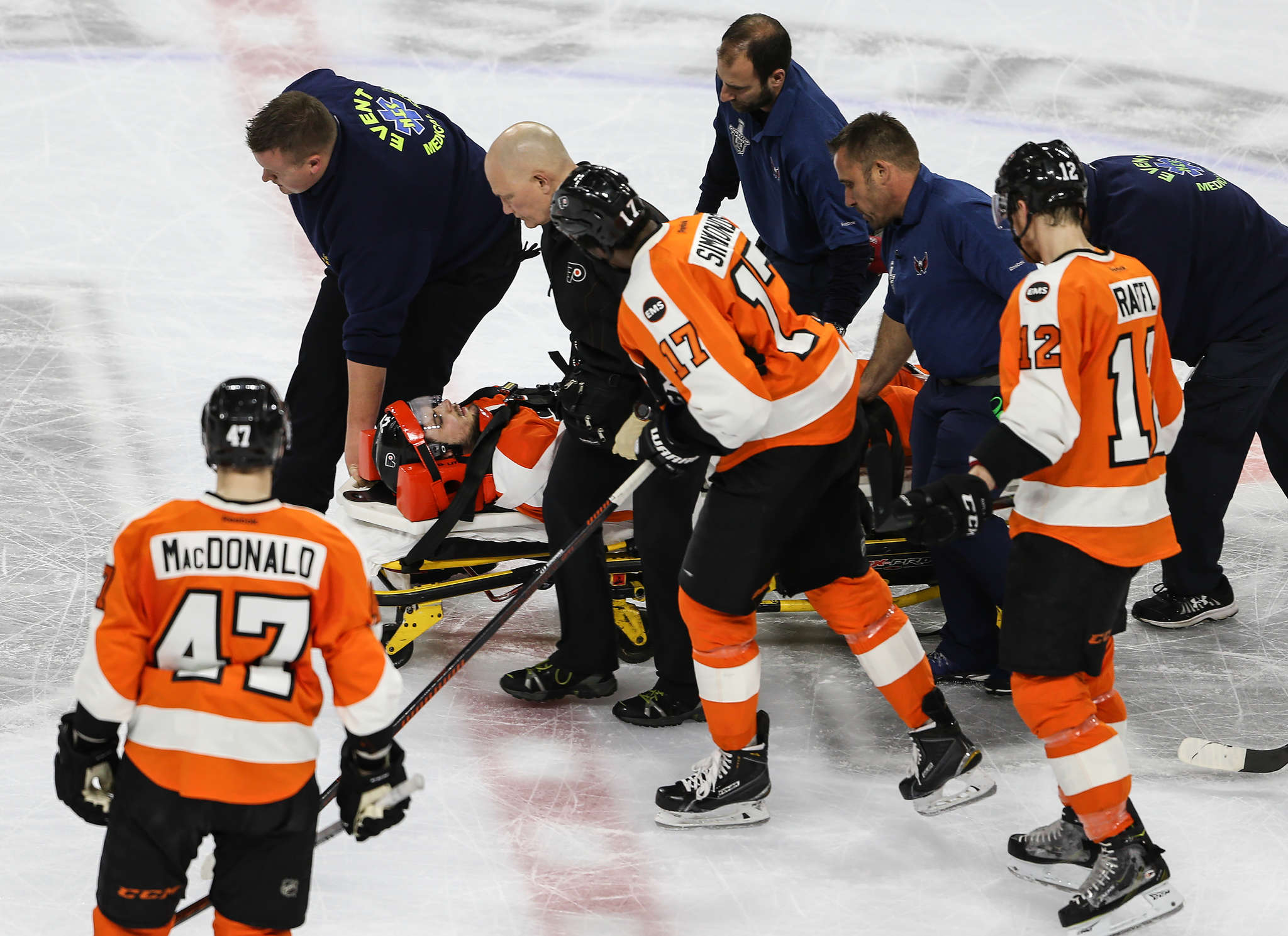 Scott Laughton is taken off the ice after sliding headfirst into the boards. STEVEN M. FALK / Staff Photographer