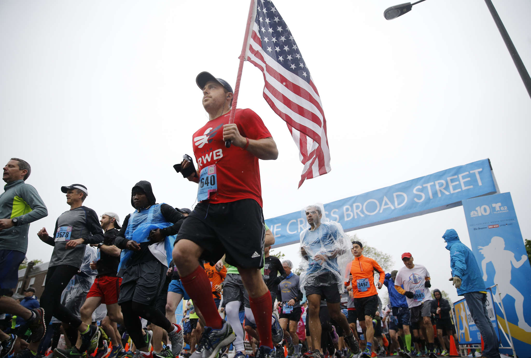 Ali Buchalter of New York City took on the 10-mile Blue Cross Broad Street Run while carrying the flag on Sunday. Some of the almost 40,000 participants said they were running in memory of others.